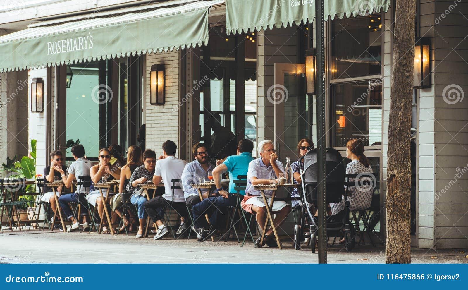 De mensen zitten buitenkant dichtbij koffie