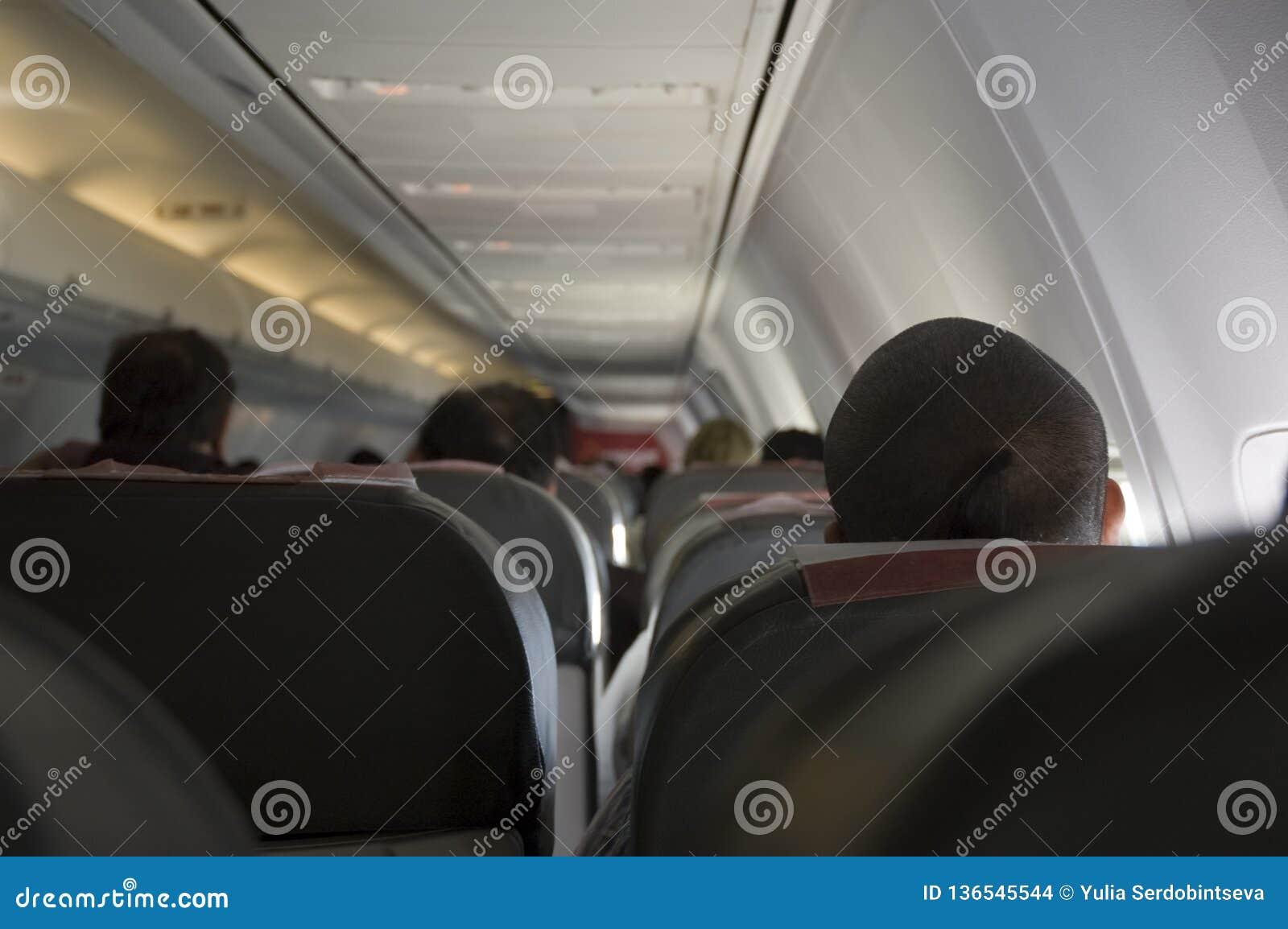 De mensen zitten in de vliegtuigencabine en het wachten op vertrek