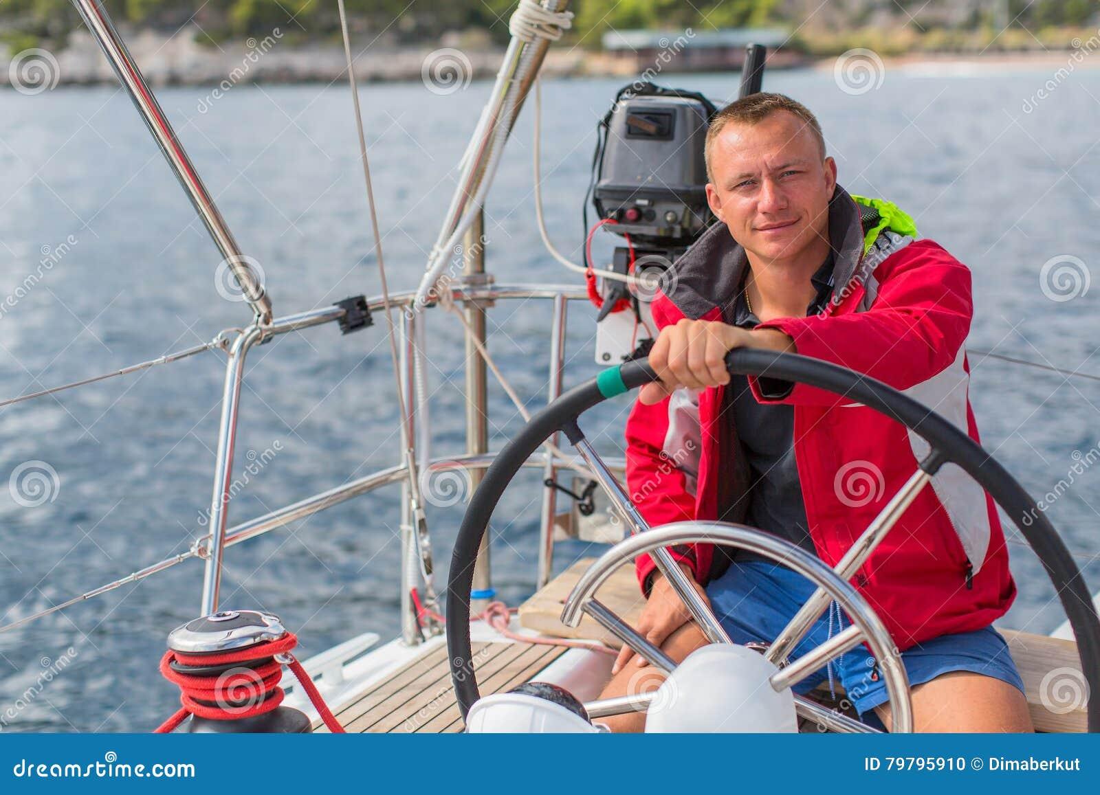 De mensenkapitein stuurt boot varend jacht op het overzees Sport