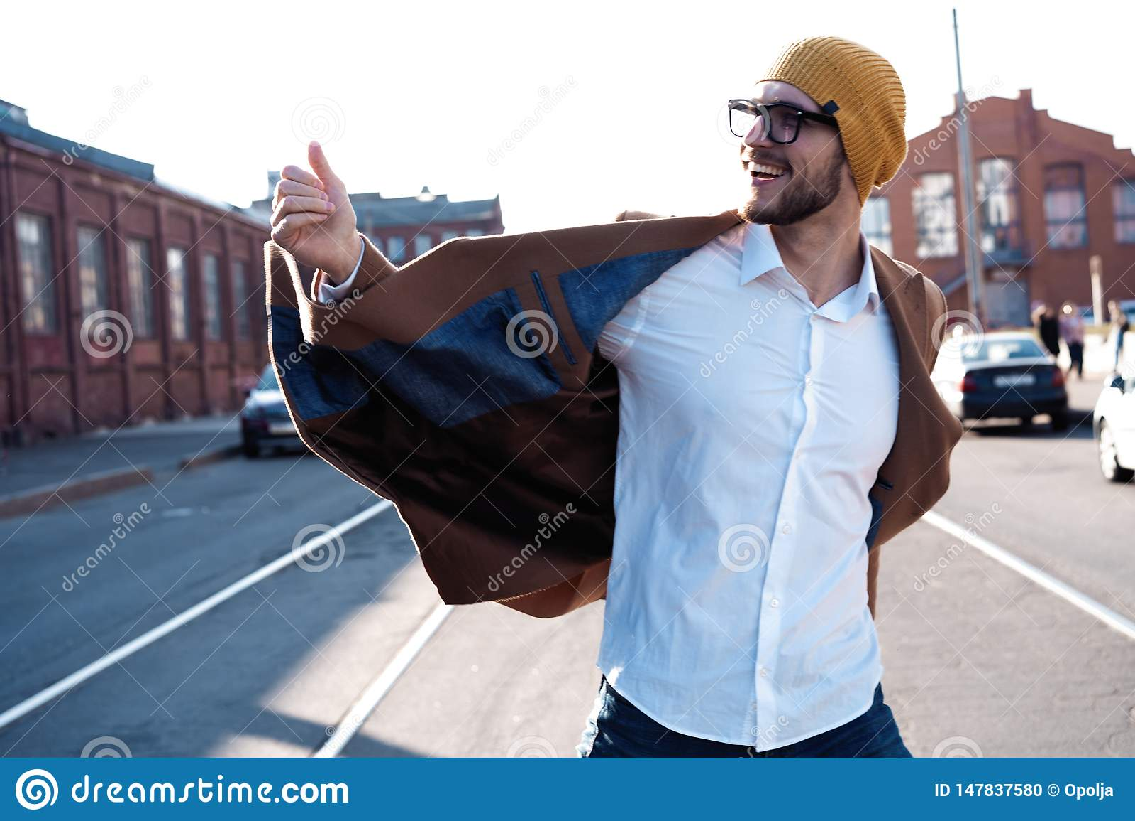 De mensenportret van de manier Jonge mens in glazen die laag dragen die onderaan de straat lopen