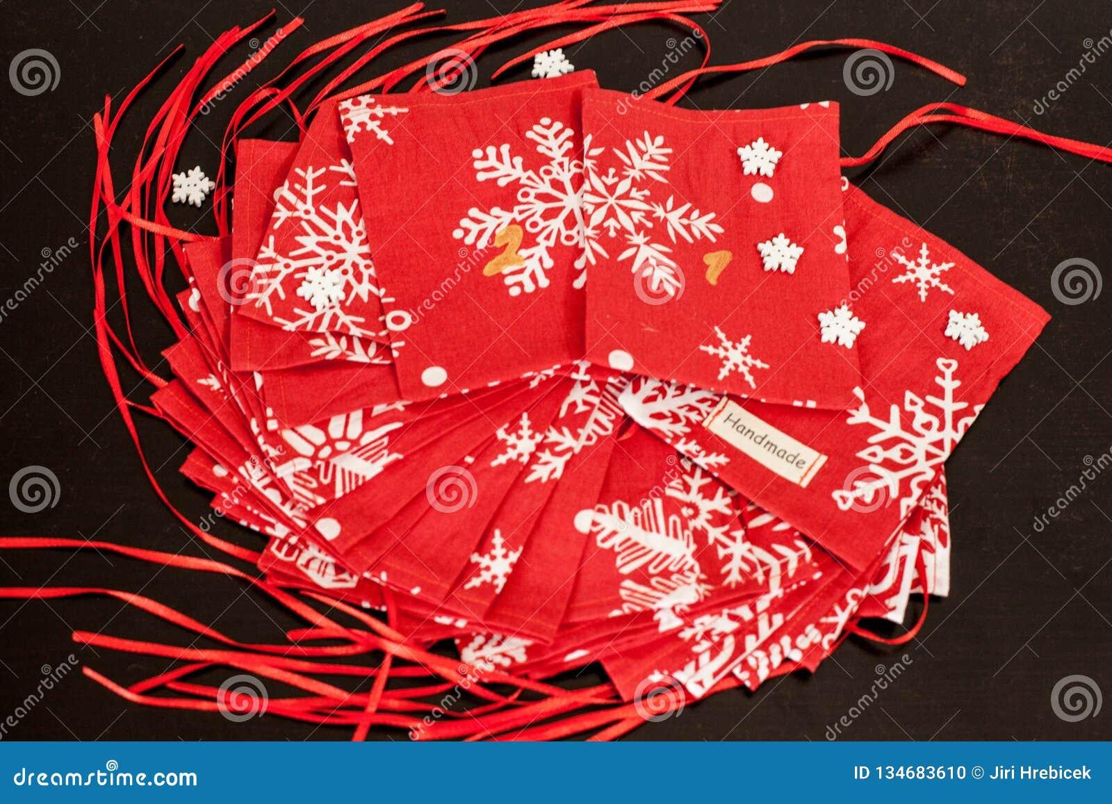 De met de hand gemaakte kalender van de Kerstmiskomst voor kinderen, rode komst genummerd zakken klaar om met speelgoed worden op