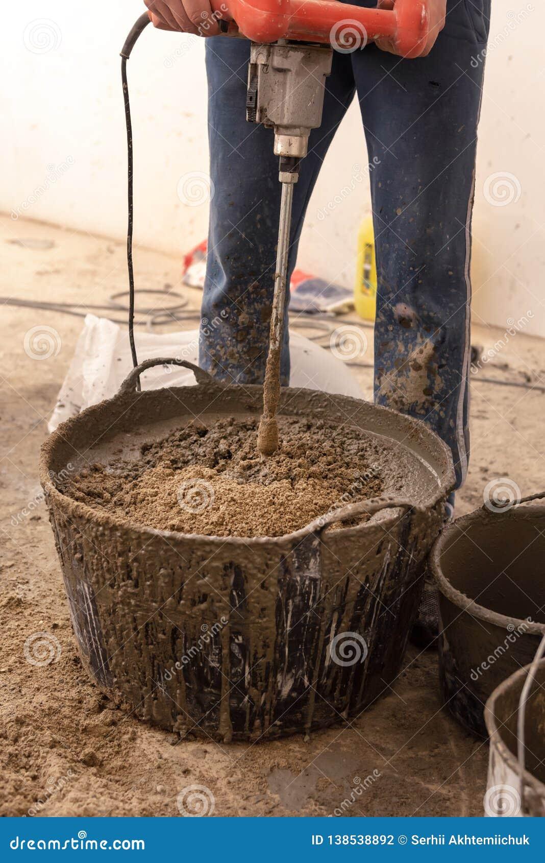 De metselaar kneedt cementmortier voor het gieten van concrete screed