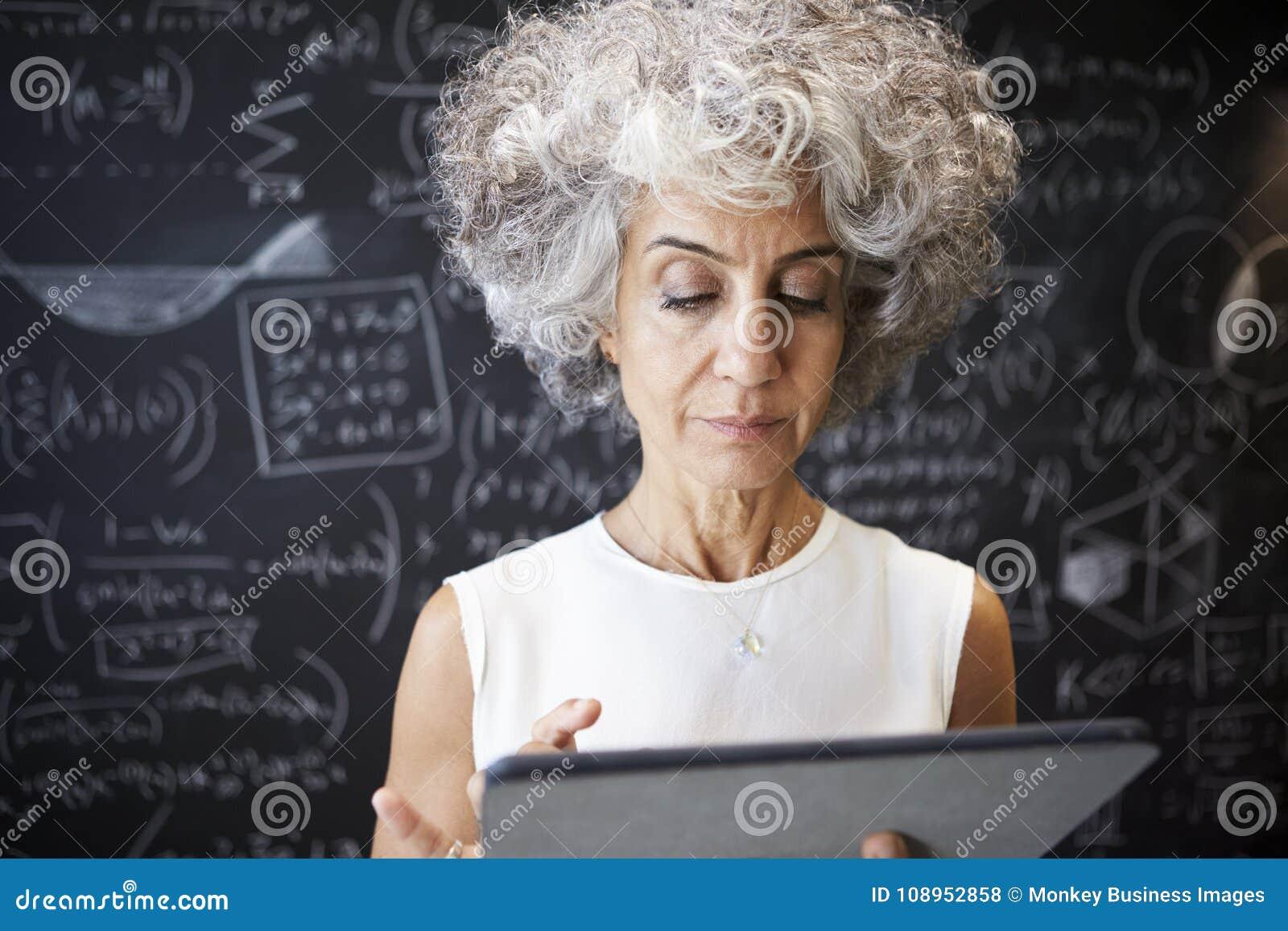 De midden oude academische vrouw die tablet gebruiken, sluit omhoog