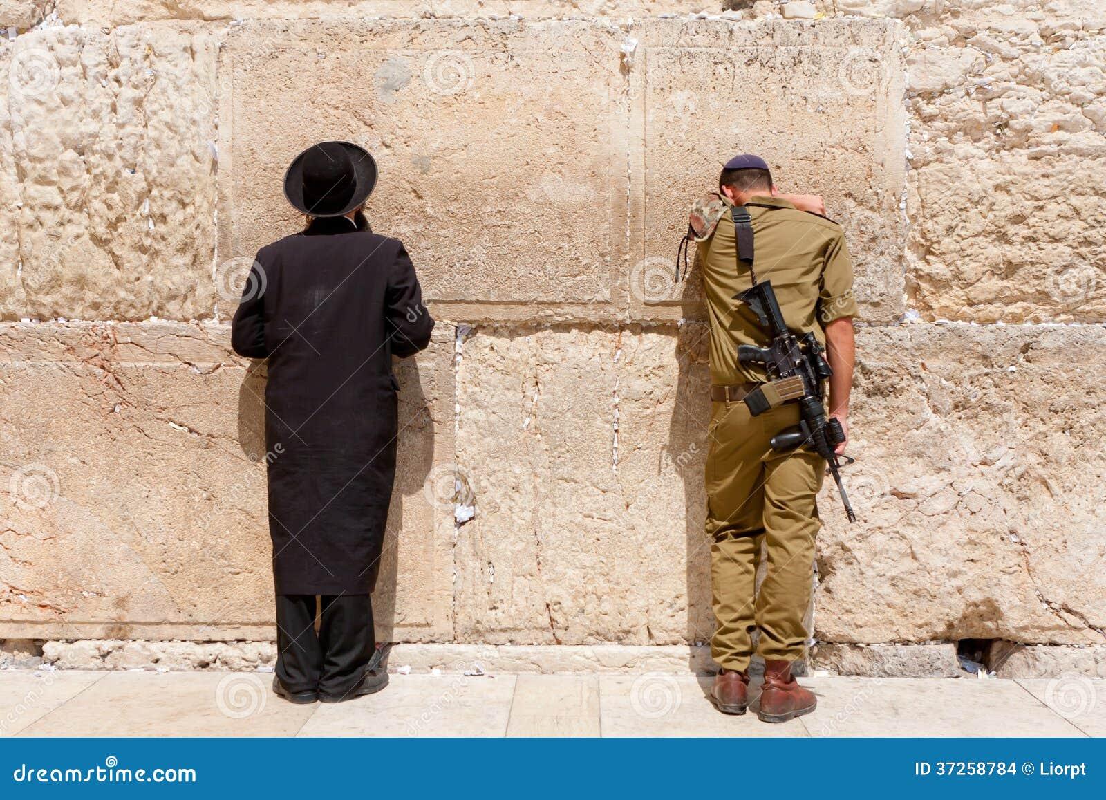 De militair en de orthodoxe Joodse mens bidden bij de westelijke muur, Jeruzalem