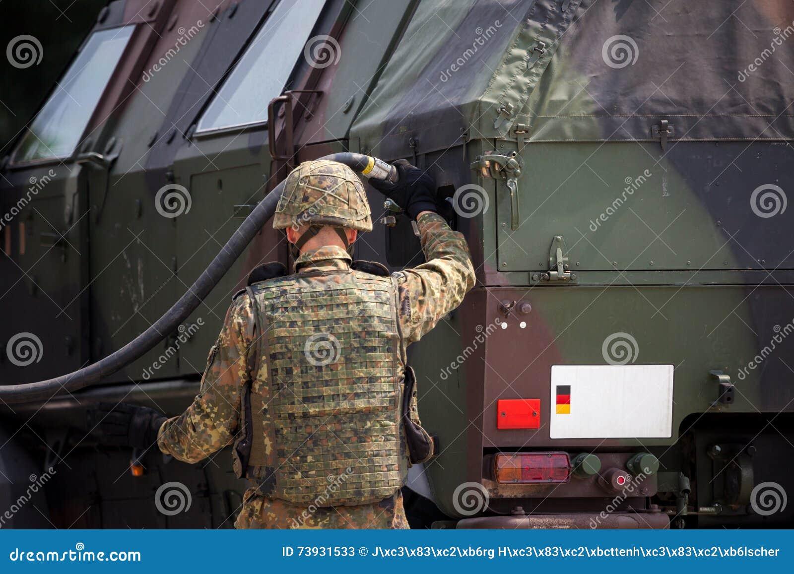 De militair voorziet een militaire gepantserde vrachtwagen van brandstof