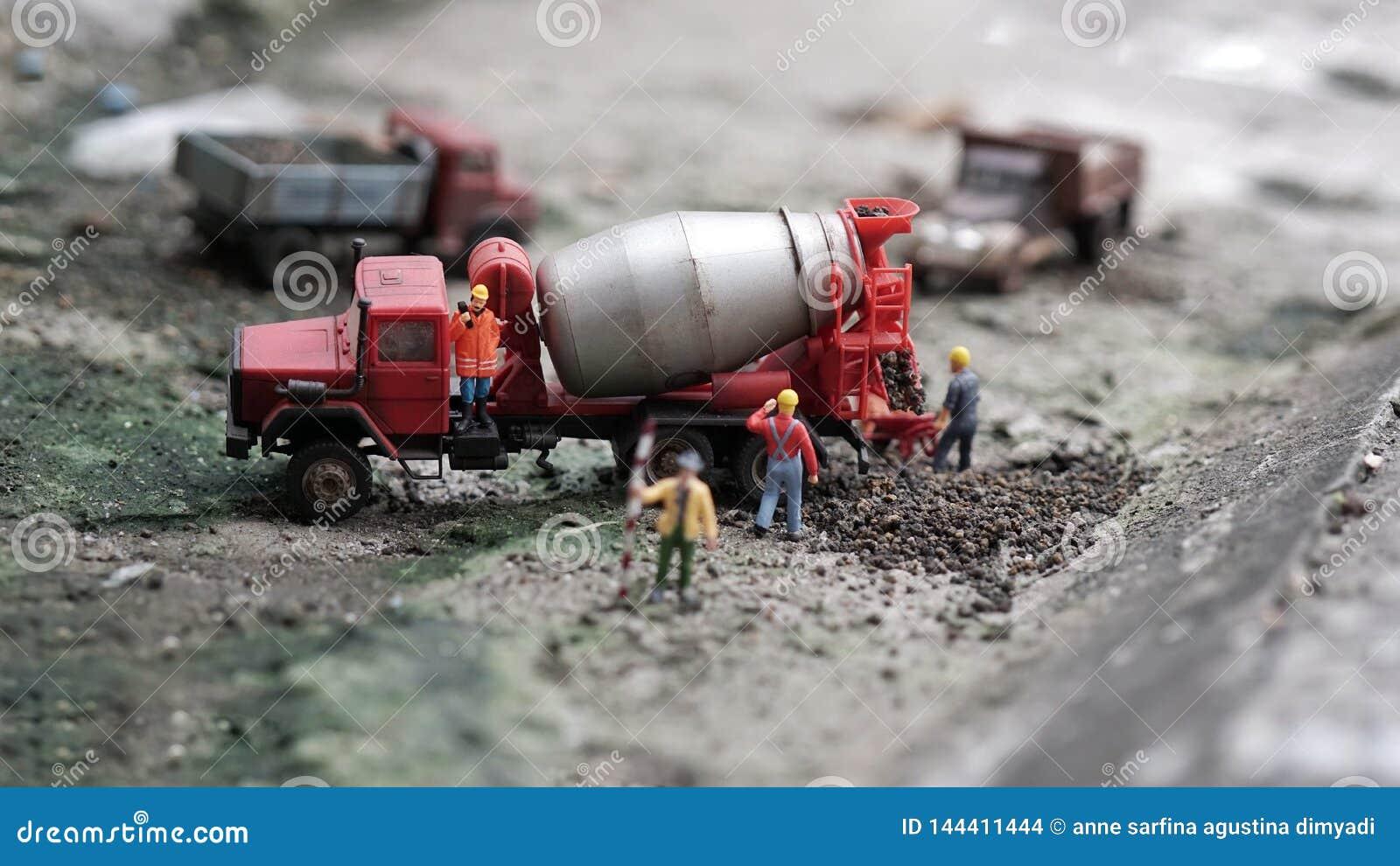 De miniatuurarbeiderswerken met de vrachtwagen van de cementmixer