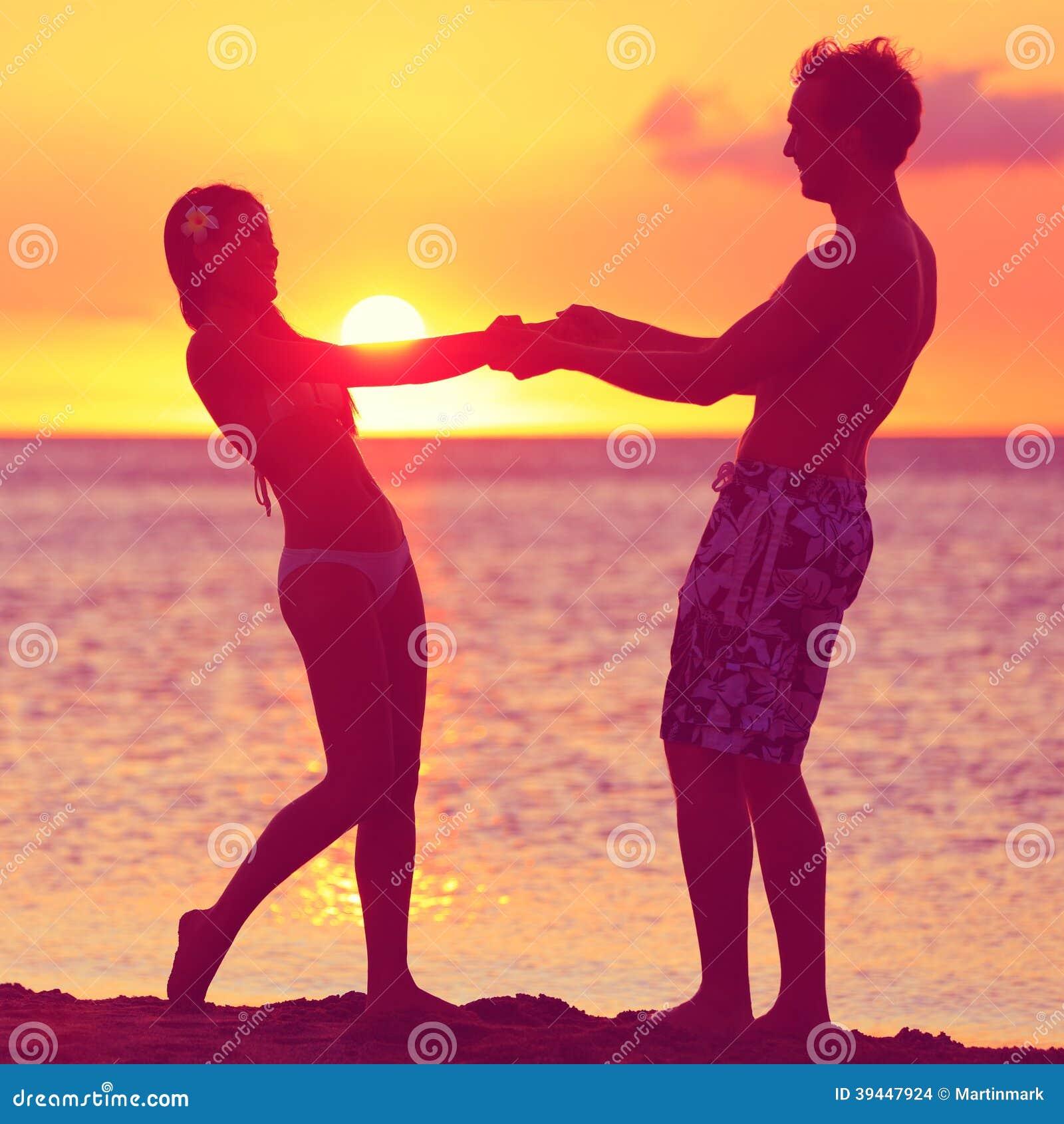 De minnaars koppelen het hebben van pret Romaans op zonsondergangstrand