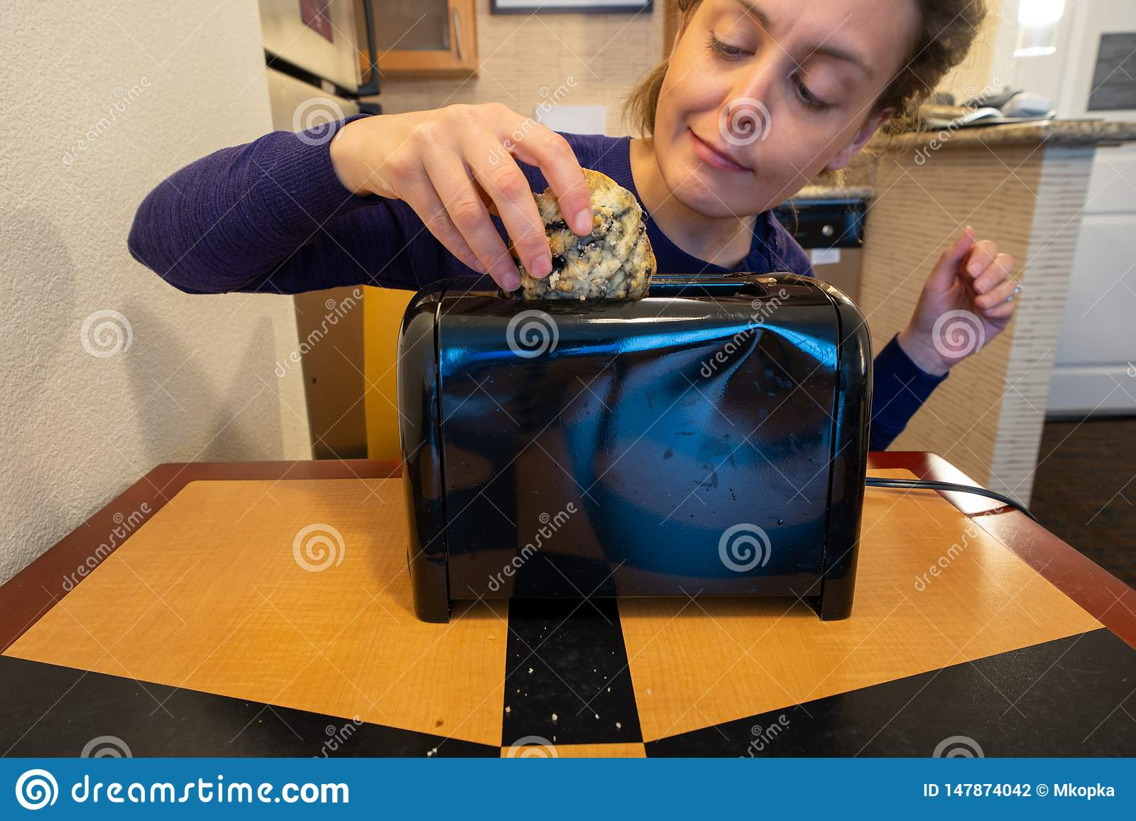 De misleide vrouw probeert om een groot bosbessenscone in een kleine die broodroostergroef te vullen, voor brood wordt bedoeld
