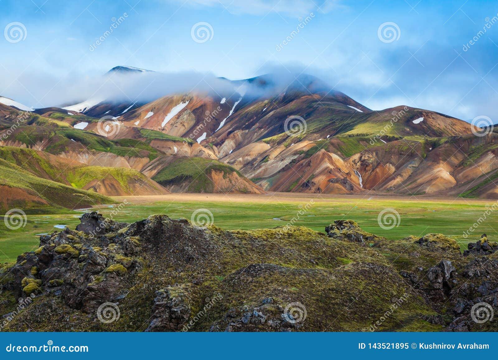 De mist ligt in de holten van kleurrijke bergen