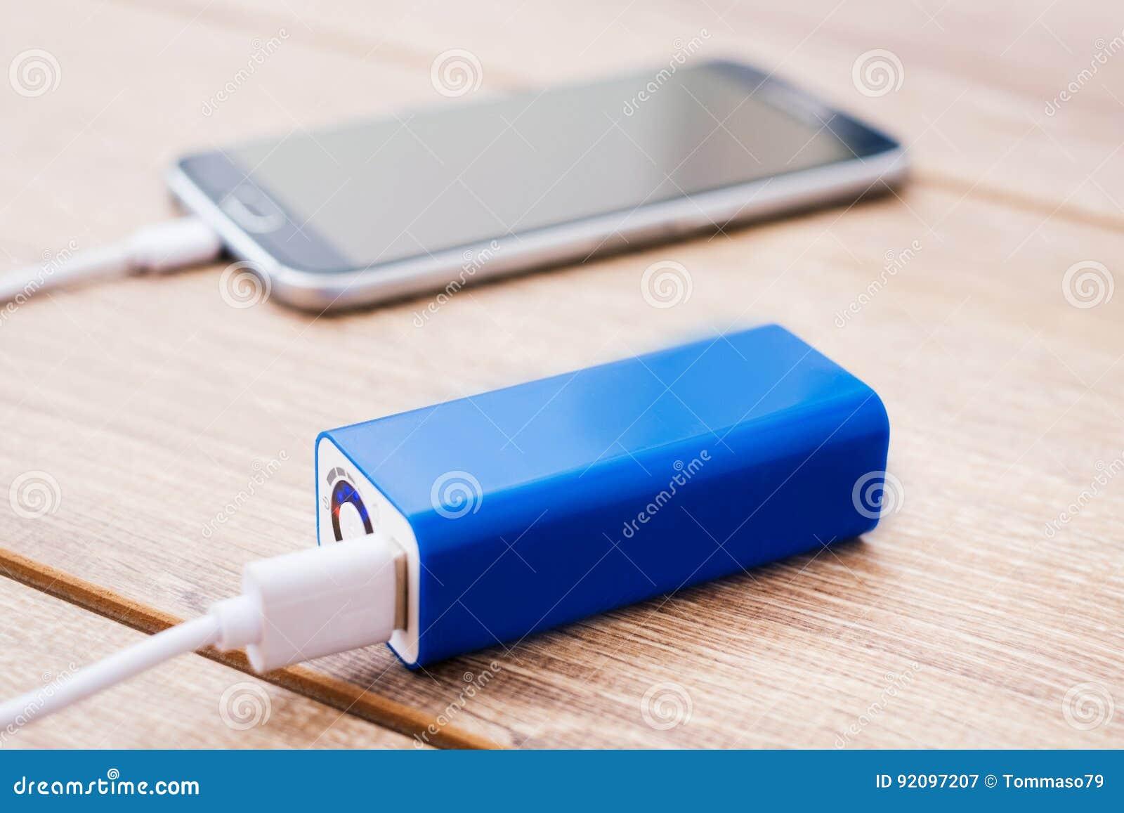 De mobiele telefoon en batterijlader van de machtsbank op een bureau