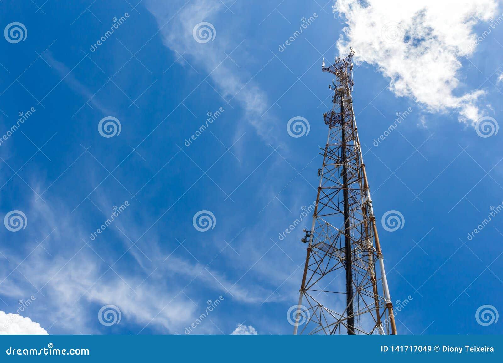 De mobiele telefoon van de communicatie toren repeaterantenne, met blauwe hemel en witte wolken