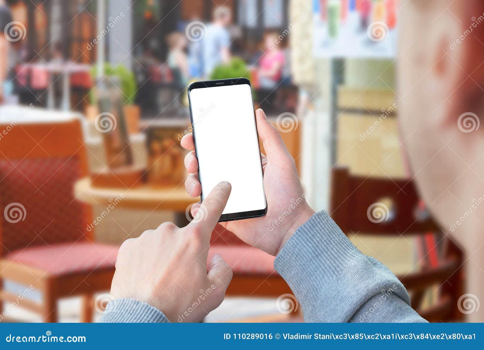 De mobiele telefoon van het mensengebruik met het geïsoleerde scherm voor model in koffiewinkel