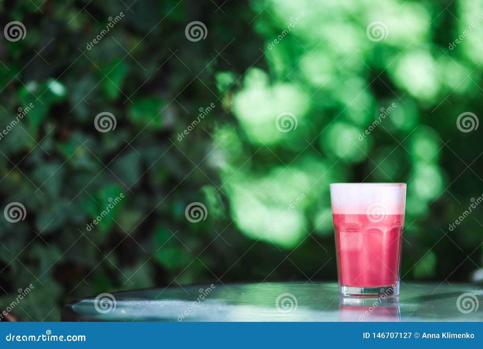 De moda, café del inconformista Un vidrio de capuchino rosado de la fresa en el fondo verde de las hojas Humor del resorte