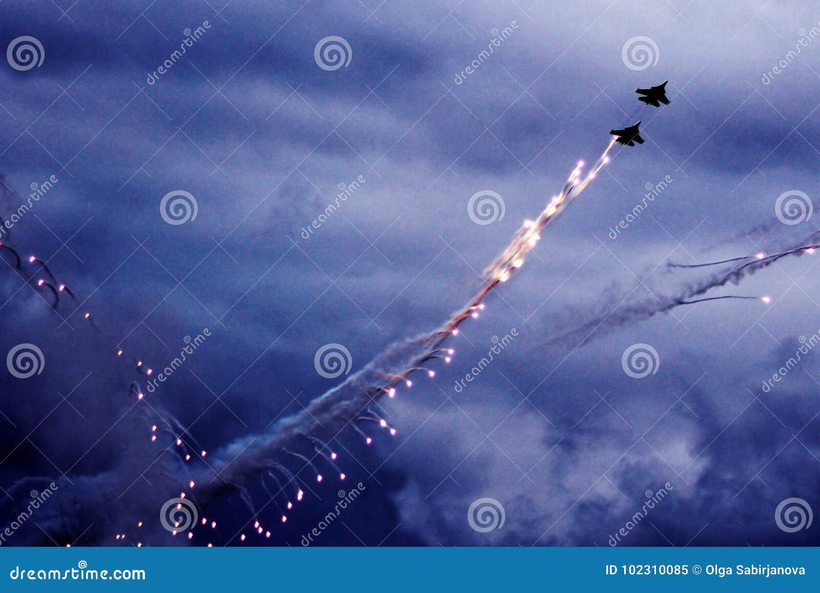 De moderne straalvechter steekt een reeks gloed op de blauwe hemel in brand Wolkencondensatie op de vleugels