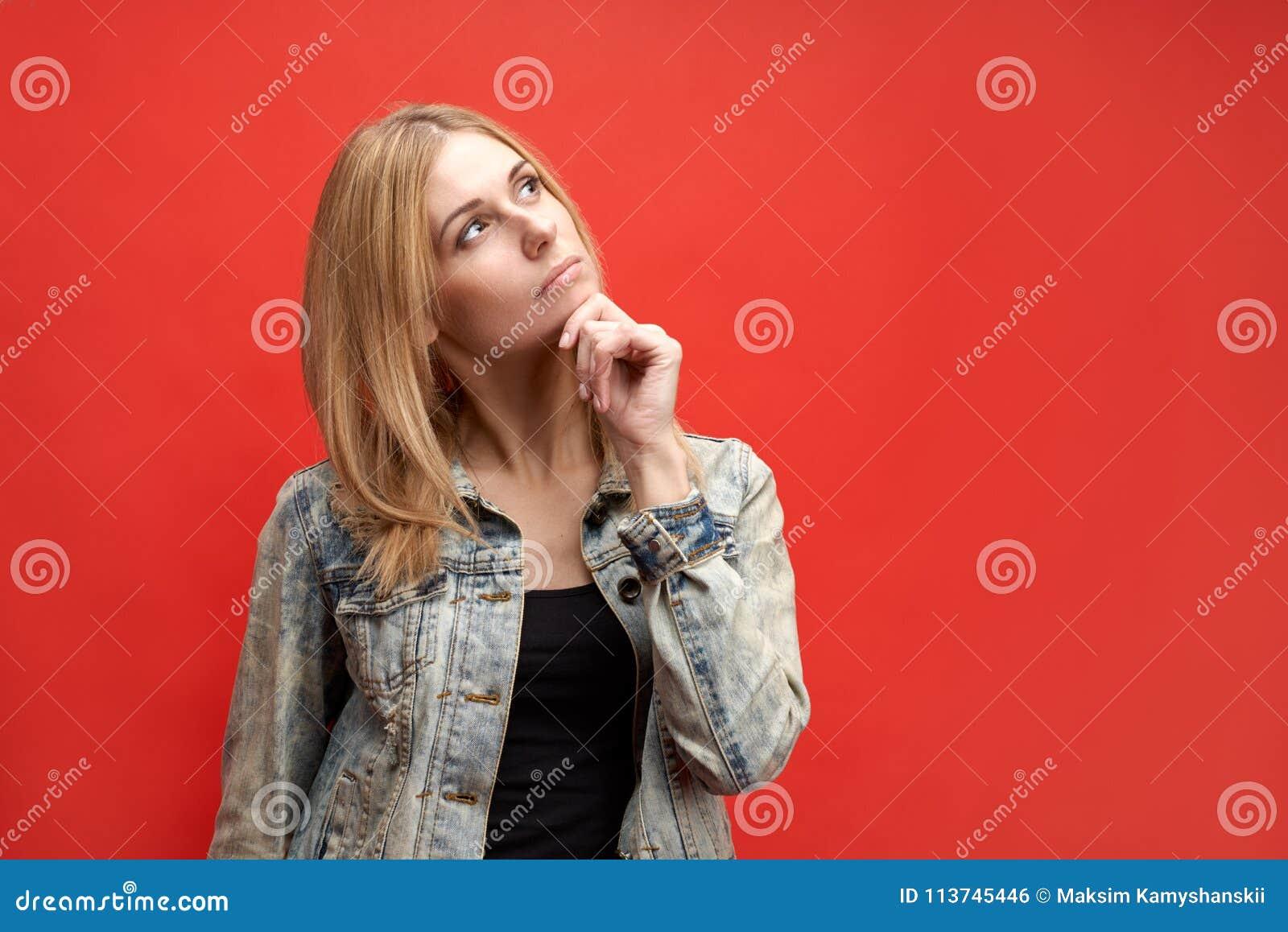 De modieuze aantrekkelijke slanke jonge vrouw van de blondestudent houdt zorgvuldig haar kin en kijkt omhoog met een peinzende ui