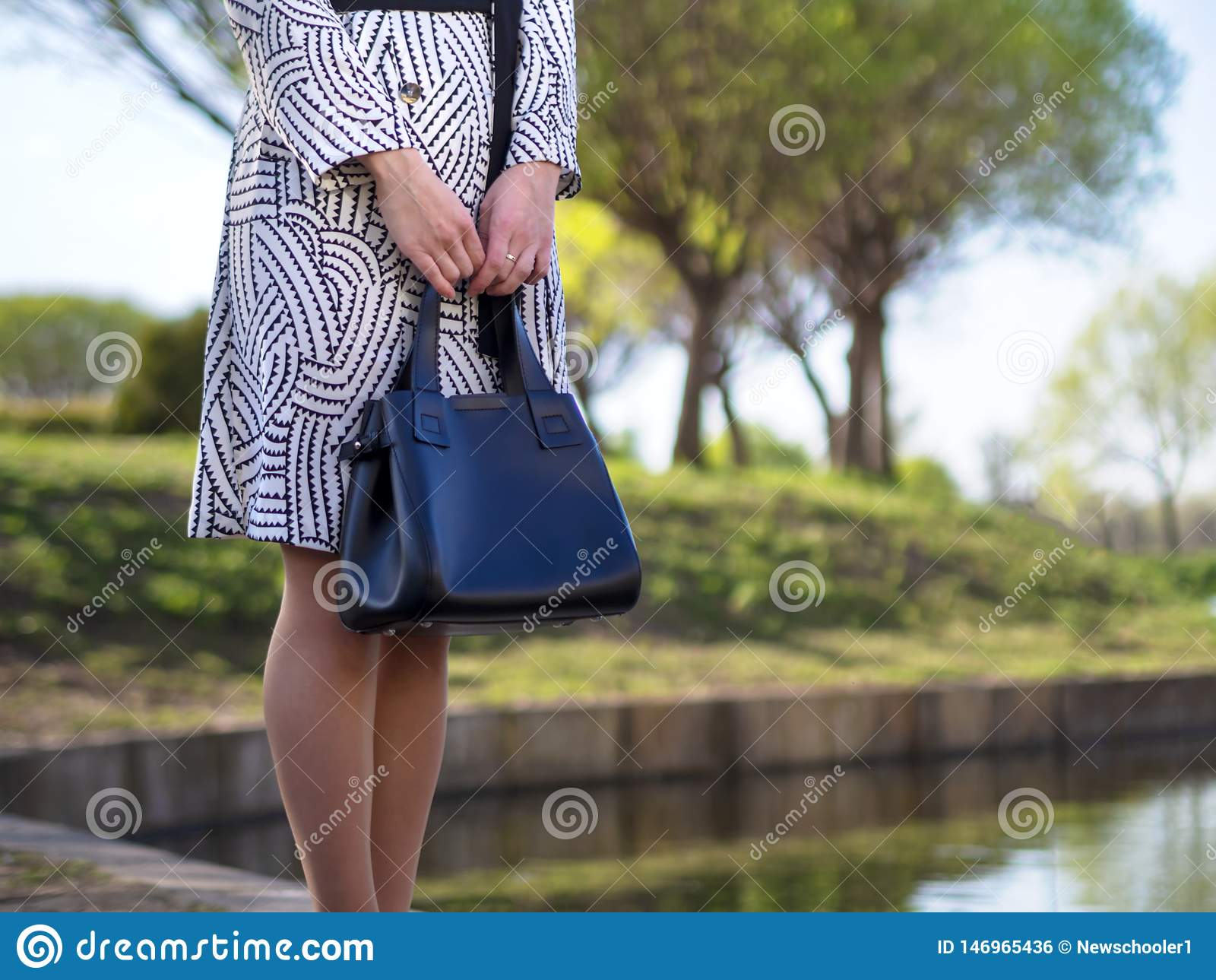 De modieuze Europese jonge vrouw in een regenjas, legging, schoenen met hielen, met een zwarte leerzak in haar dient een park dic