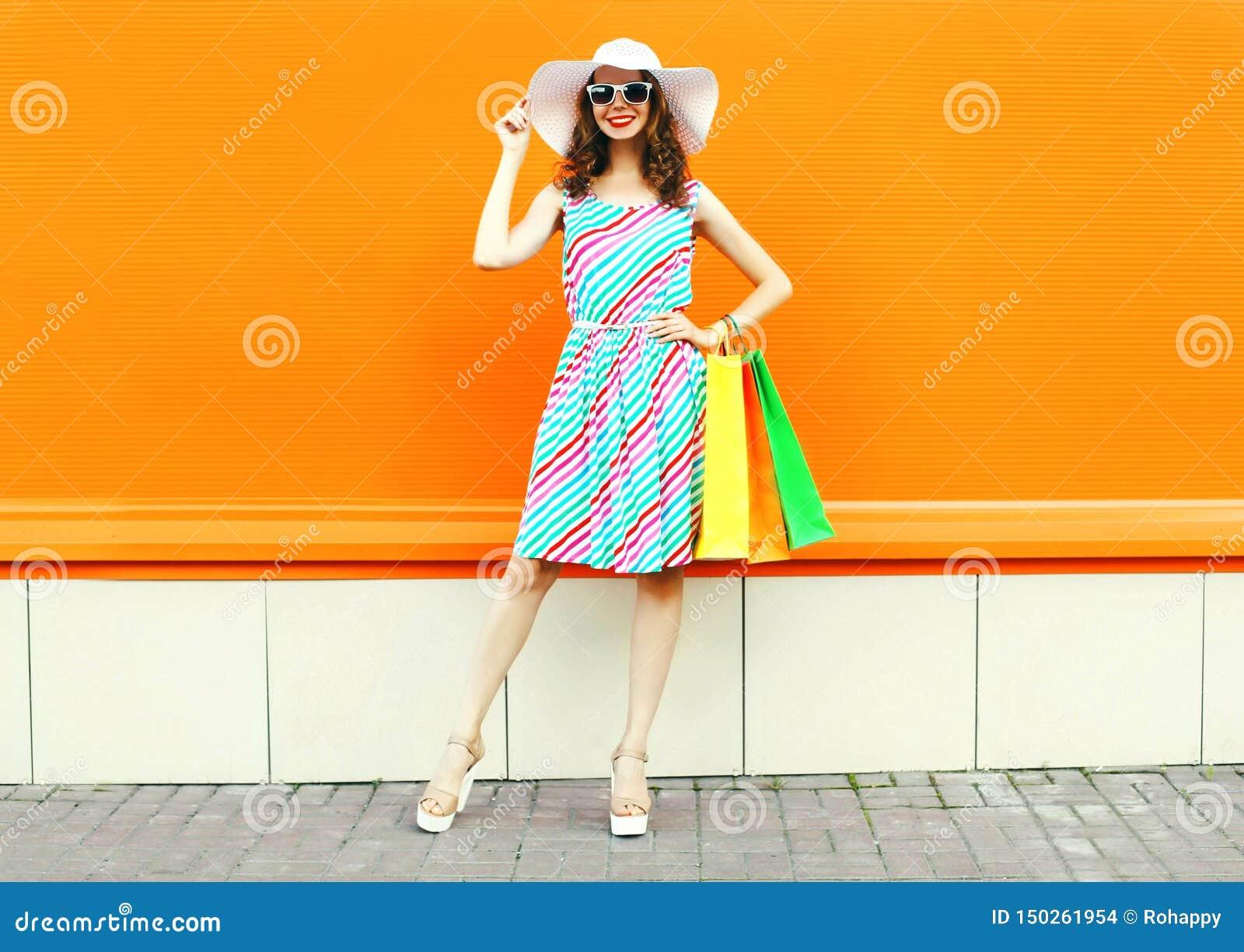 De modieuze glimlachende vrouw met het winkelen doet het dragen van kleurrijke gestreepte kleding, de hoed van het de zomerstro h