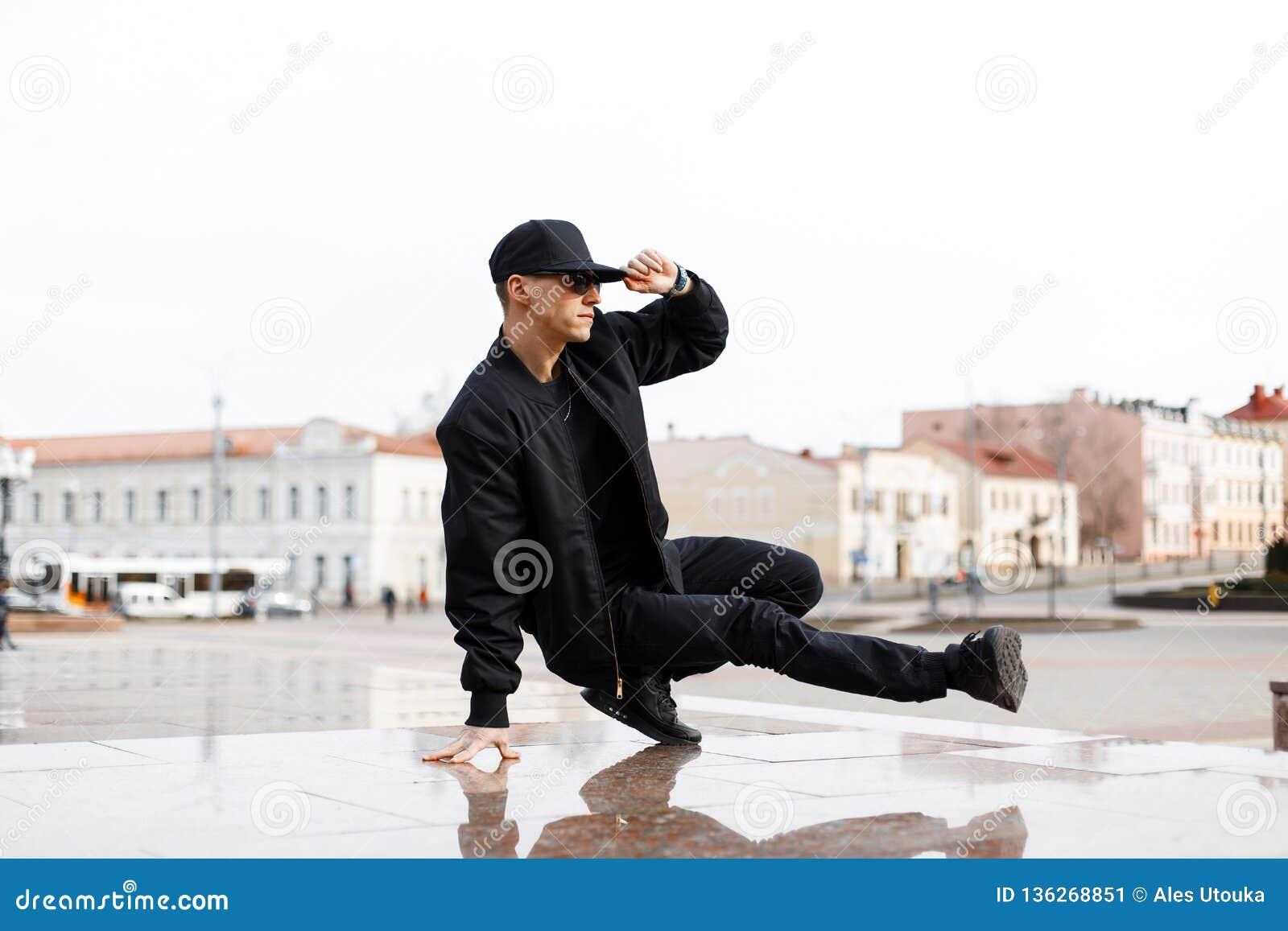 De modieuze jonge mannelijke danser in modieuze zwarte kleren die blake danst op een straat in de stad op een de herfstmiddag dan