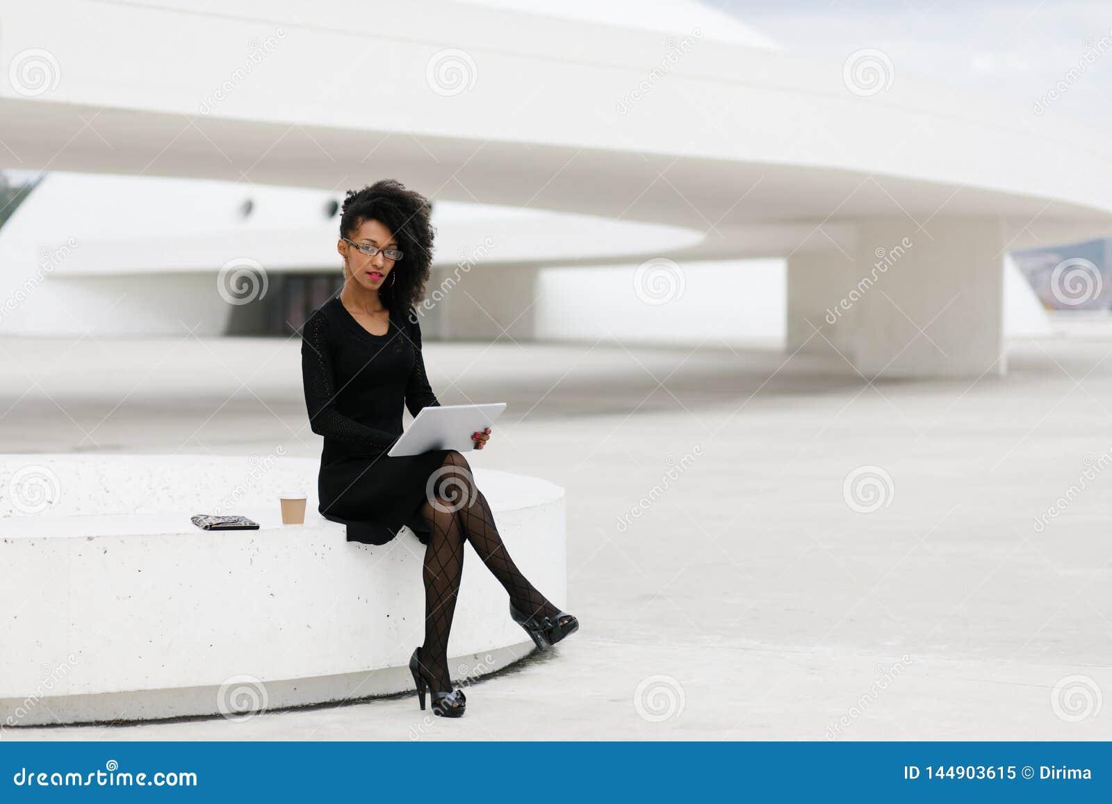 De modieuze jonge professionele vrouw die van het afrohaar tablet gebruiken