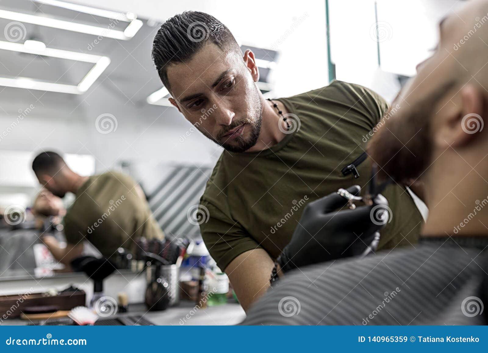 De modieuze mens met een baard zit voor de spiegel bij een herenkapper De baard van de mensen van kappersversieringen met schaar