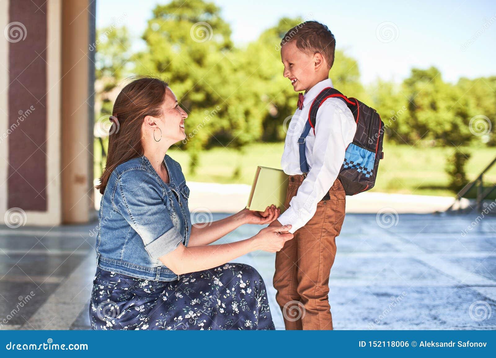 De moeder begeleidt het kind aan school het mamma moedigt student aan die hem begeleiden aan school een gevende moeder bekijkt te