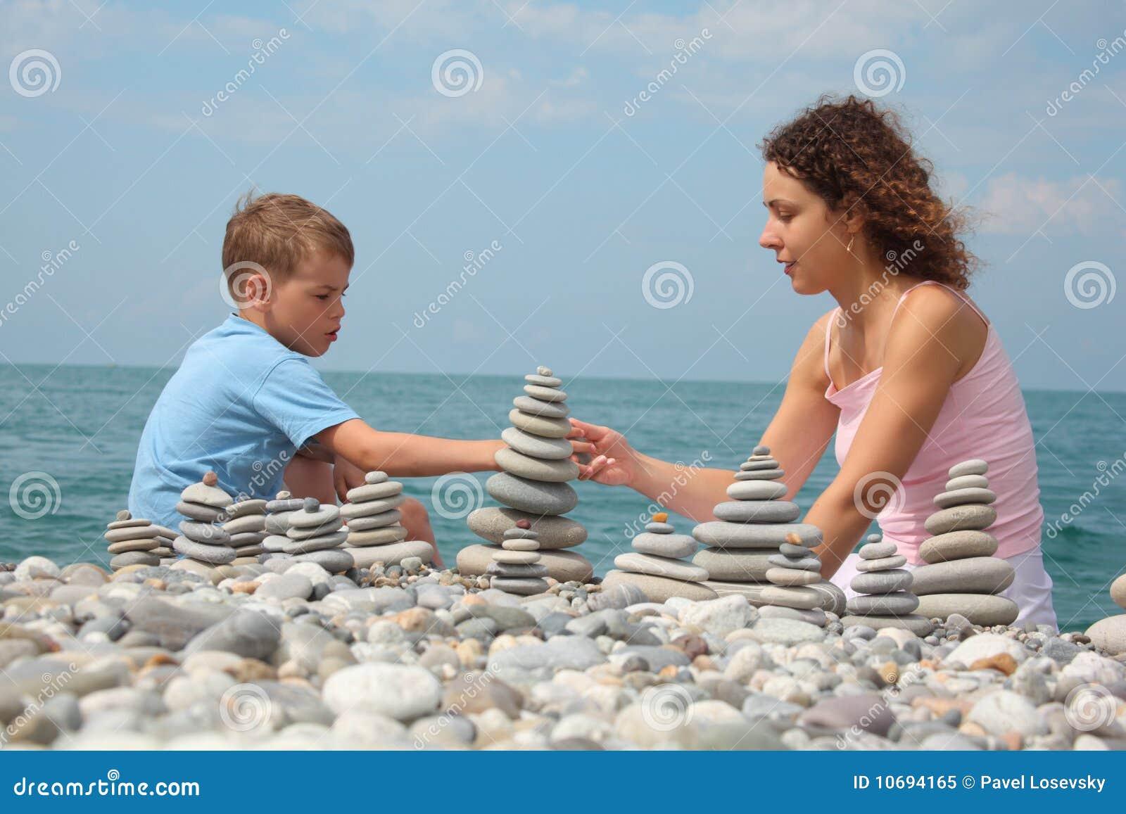 De moeder en de zoon bouwen steenstapels op strand