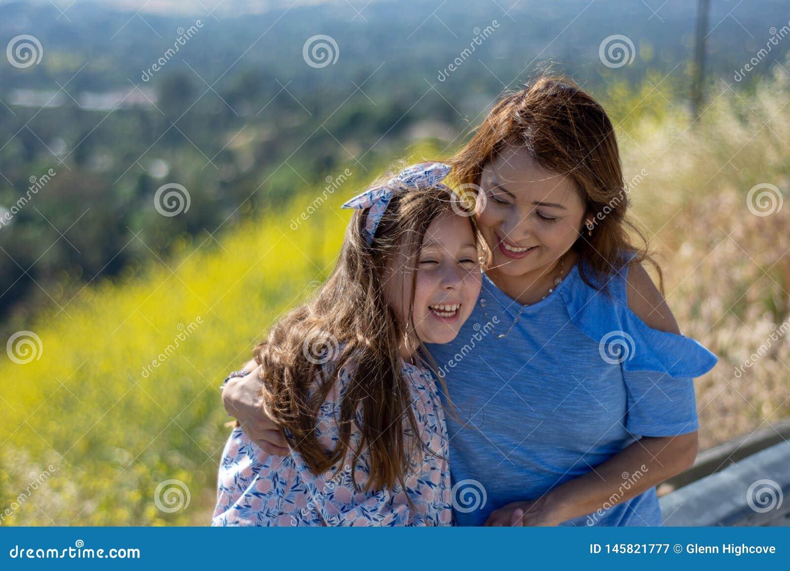 De Moeder en de Dochter die van Latina en op een heuvel voor gele bloemen glimlachen lachen