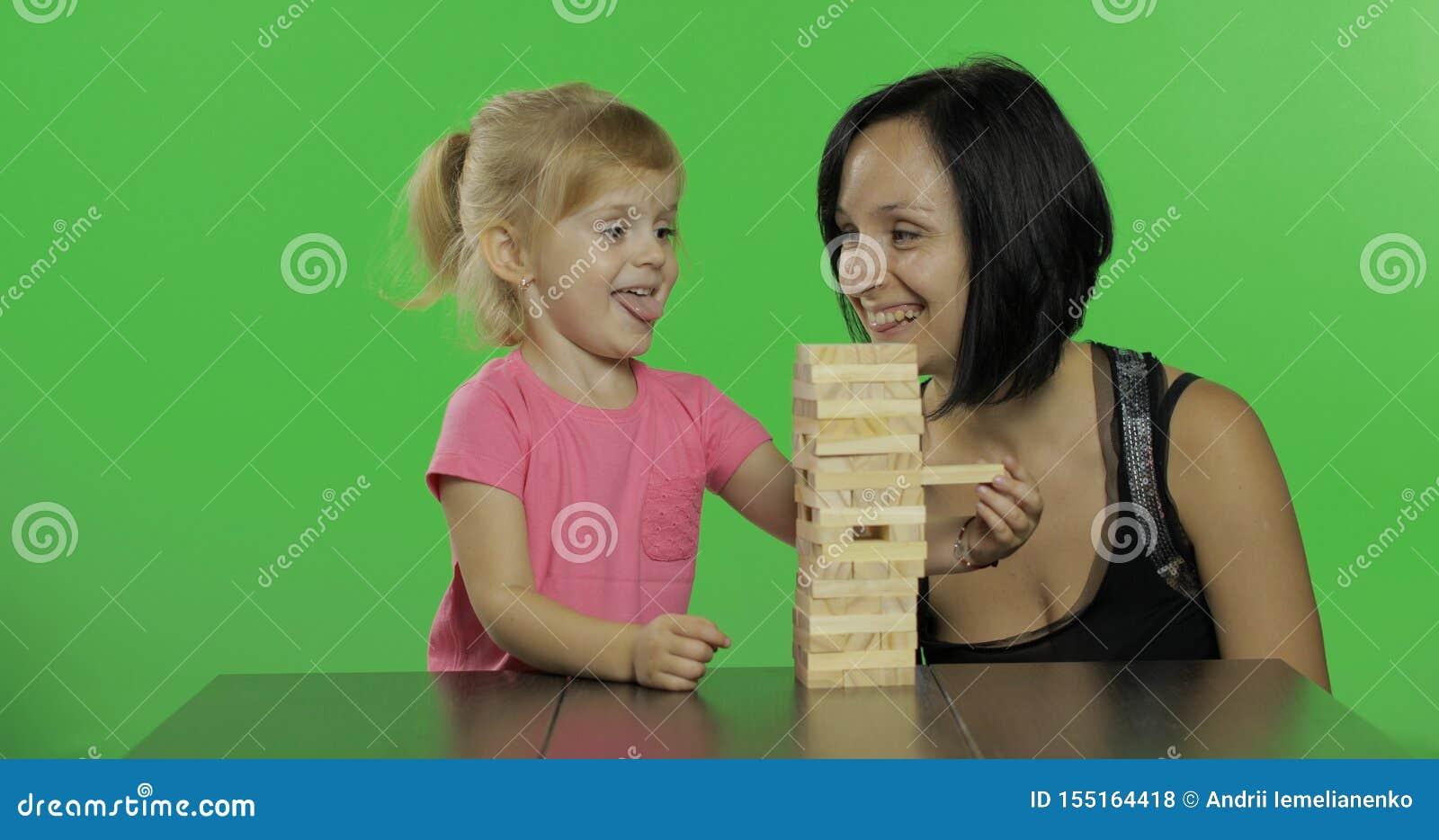 De moeder en de dochter spelen jenga Het kind trekt houten blokken van toren