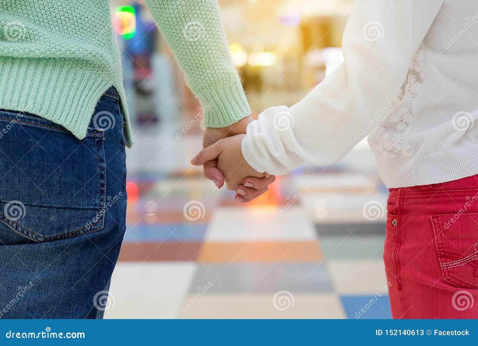 De moeder en een kindholding dienen winkelcomplex in Sluit omhoog
