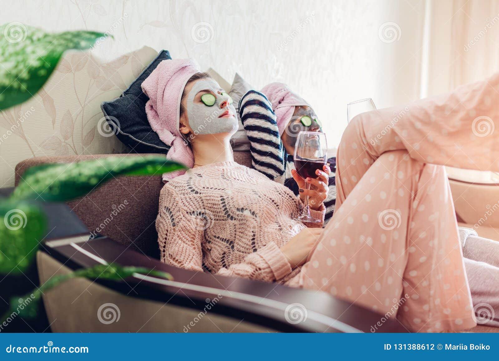 De moeder en haar volwassen dochter pasten gezichtsmaskers en komkommers op ogen toe Vrouwen die terwijl het hebben van wijn koel