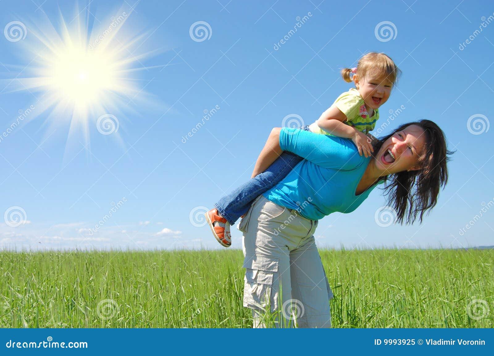 De moeder en het kind van de familie onder blauwe hemel