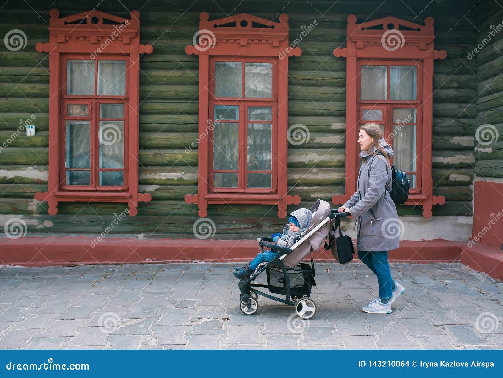 De moeder en de kleine zoon in een wandelwagen lopen op de stadsstraat langs het grote oude blokhuis