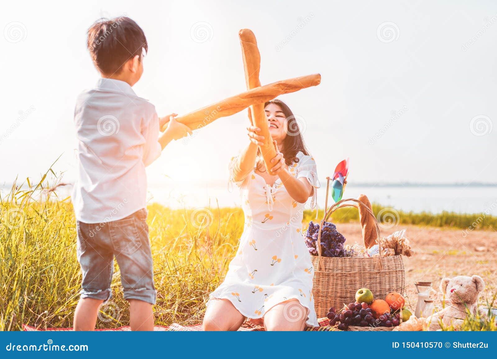 De moeder en de zoon spelen het schermen met brood samen wanneer picknick bij in openlucht dichtbij meer of rivier Mensenlevensst
