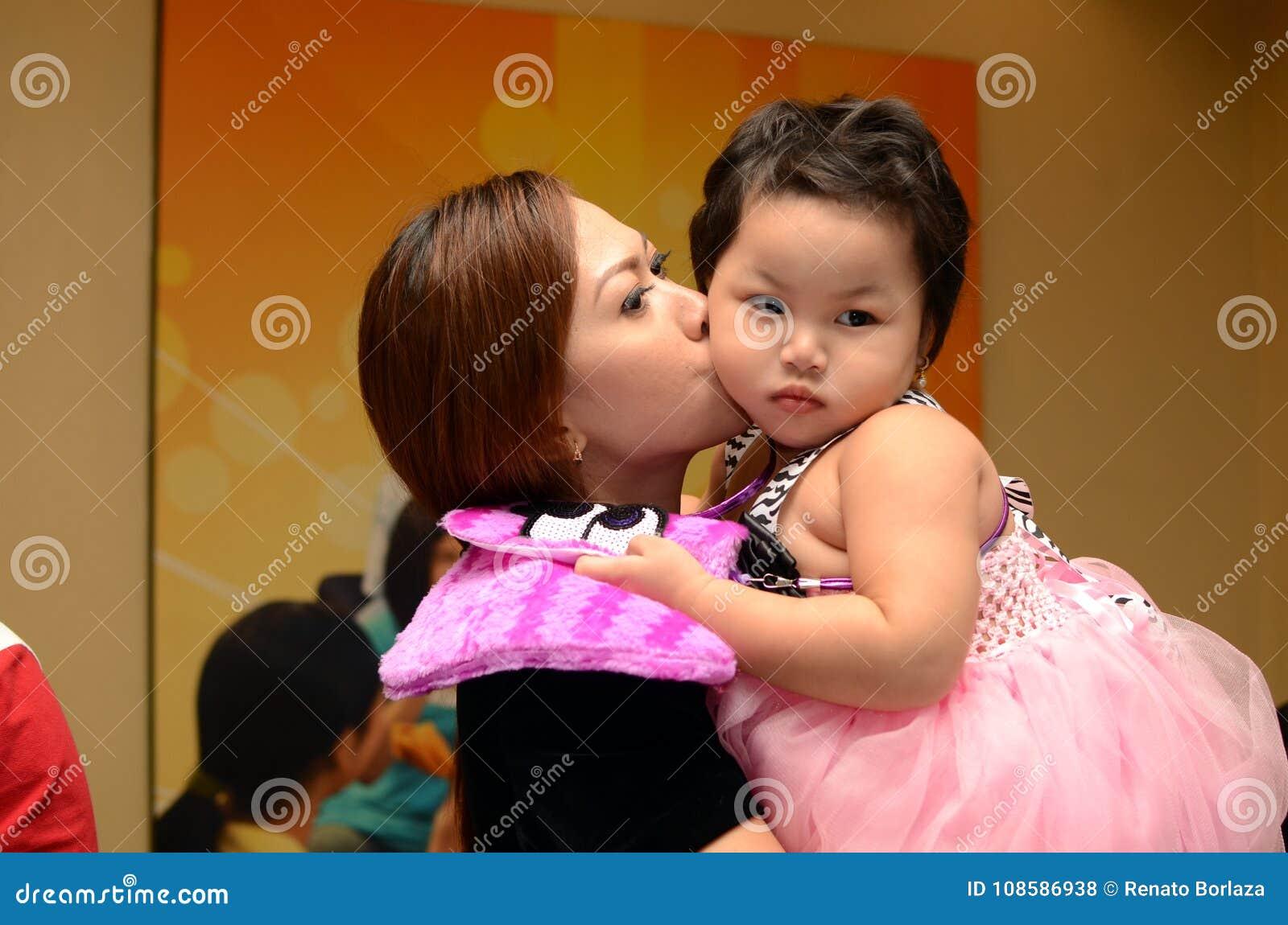 De moeder kust haar aanbiddelijk babymeisje Gedenkwaardige beelden