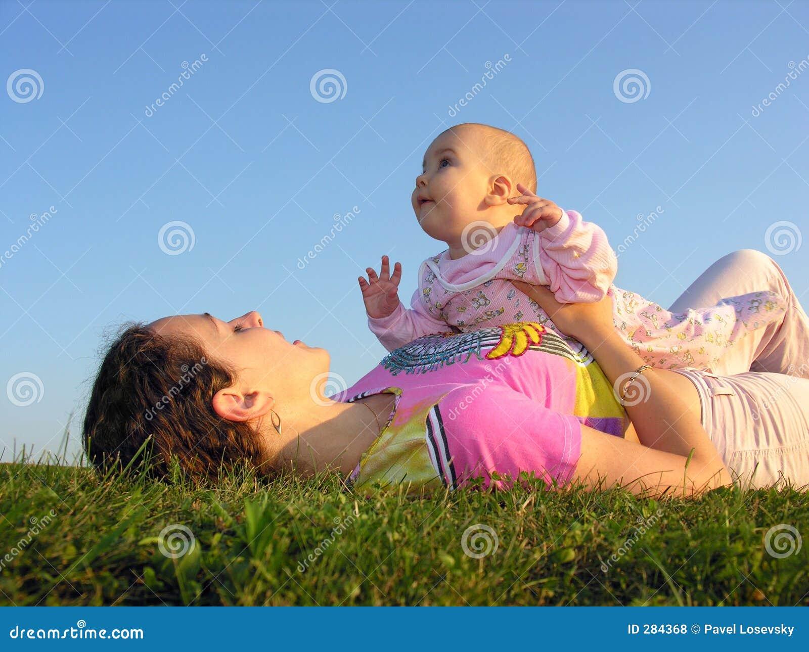 De moeder met baby op zonsondergang ligt