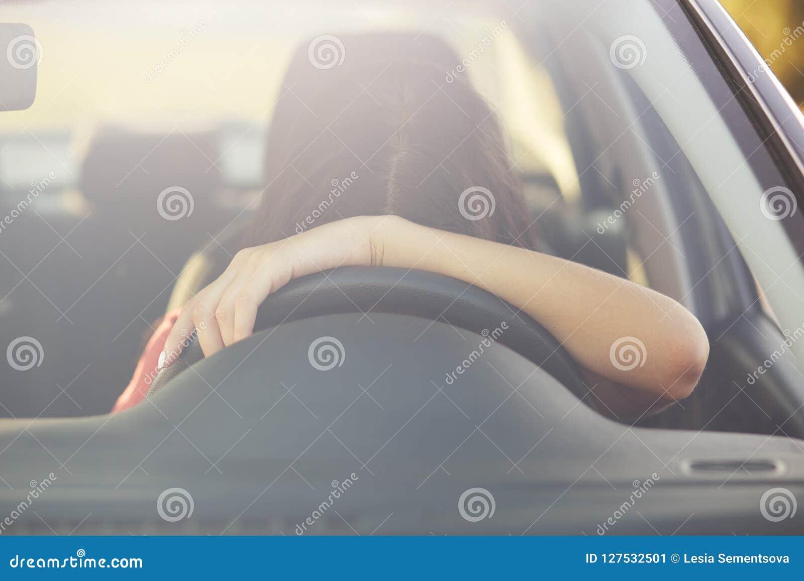 De moeheid de slapeloze vrouwelijke bestuurder op wiel leunt, houdt op om rust te hebben, stelt in auto, behandelde lange afstand