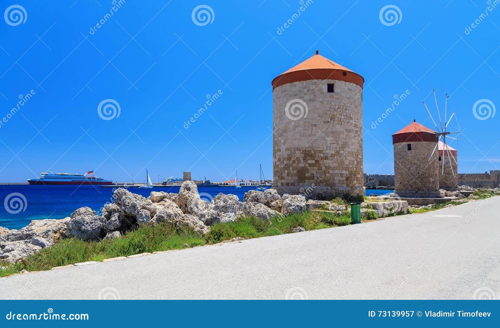 De molens van Rhodos op de achtergrond van de overzeese baai en de haven zonnige dag