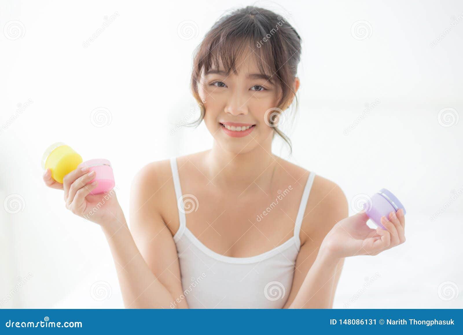 De mooie aantrekkelijke de holdingskruiken van de portret jonge Aziatische vrouw room en lotion villen voor gezicht vers en zacht