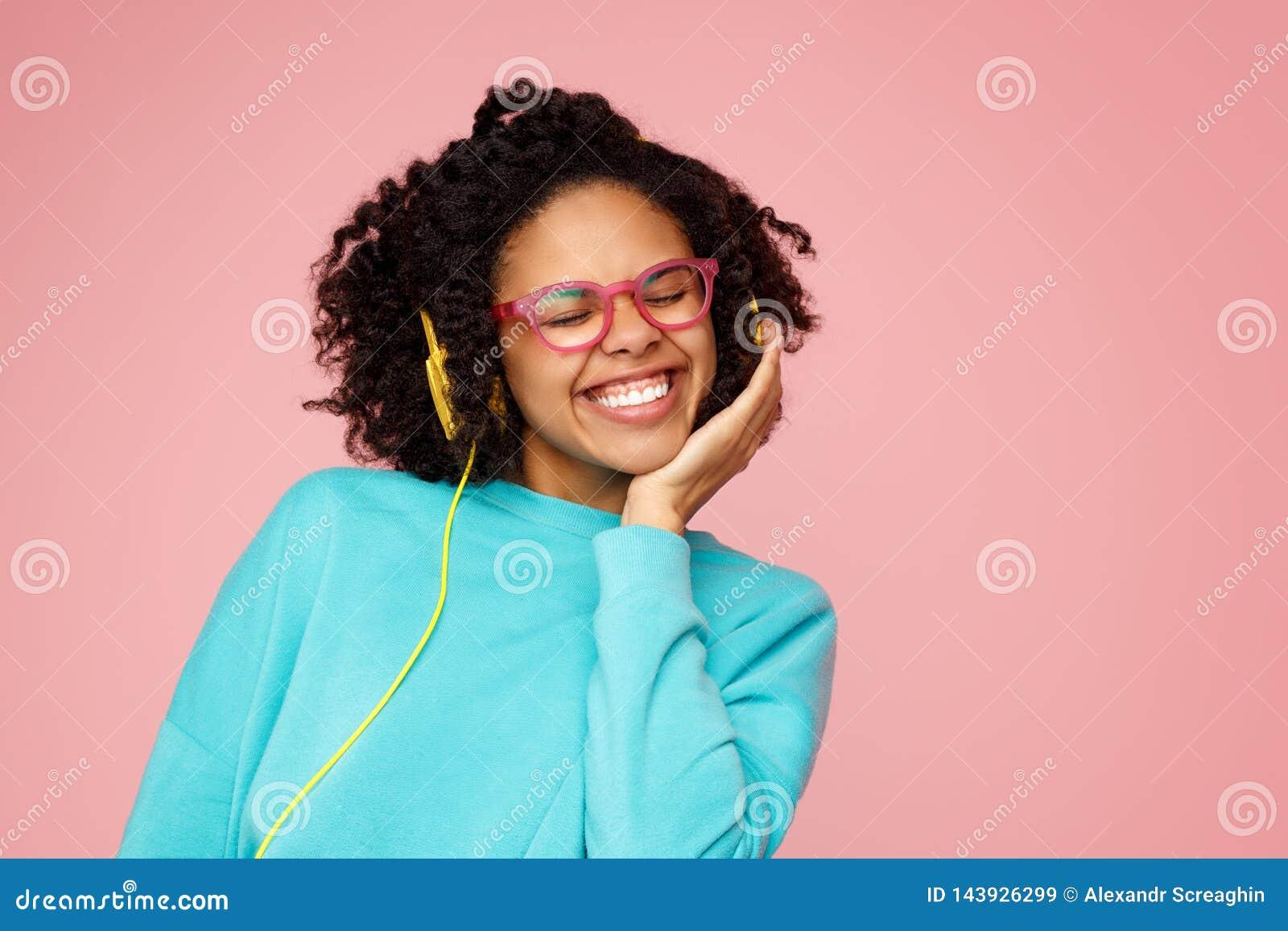De mooie Afrikaanse Amerikaanse jonge vrouw met heldere glimlach kleedde zich in vrijetijdskleding, glazen en hoofdtelefoons over