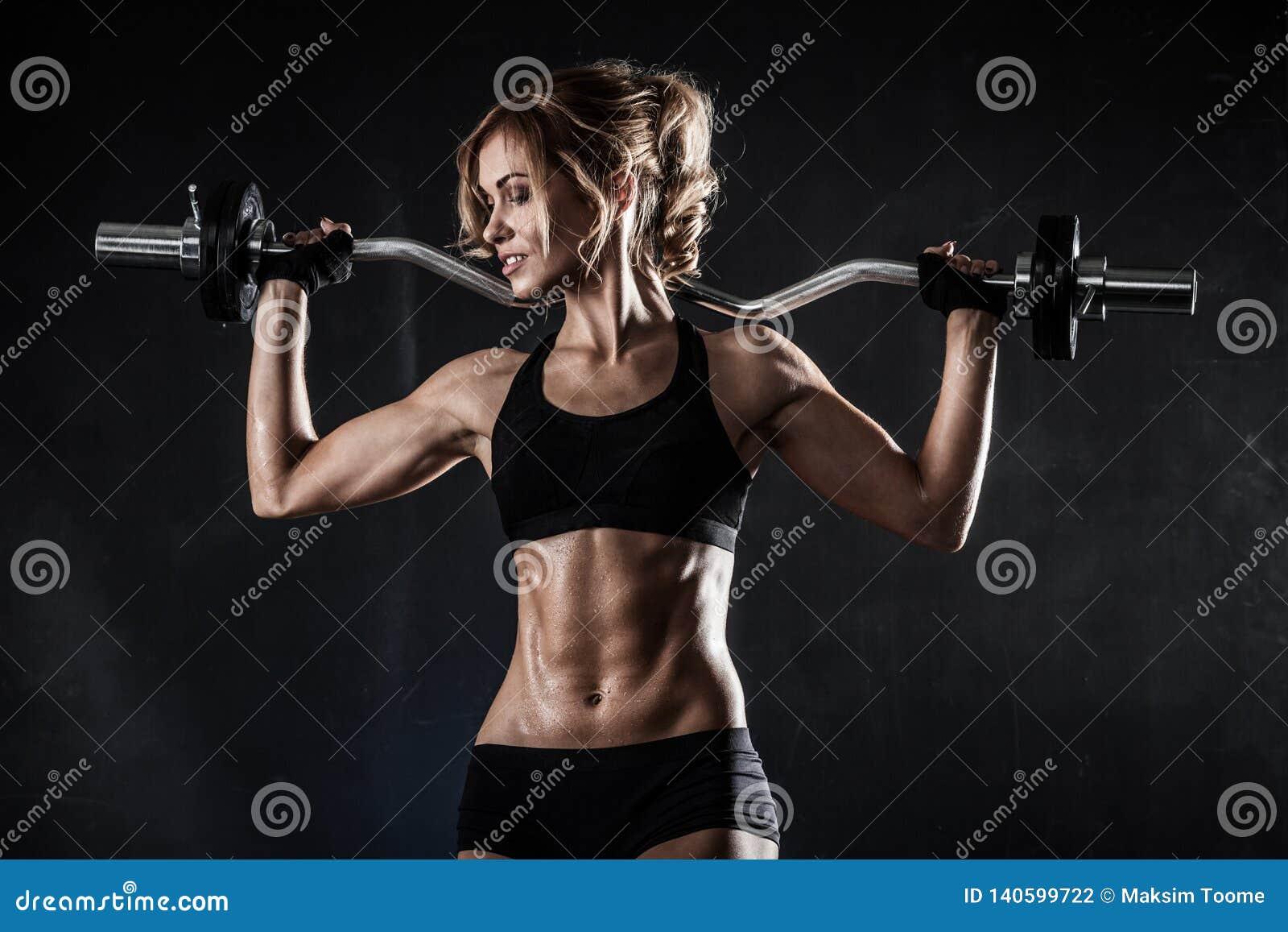 De mooie atletische vrouw maakt oefeningen met barbell