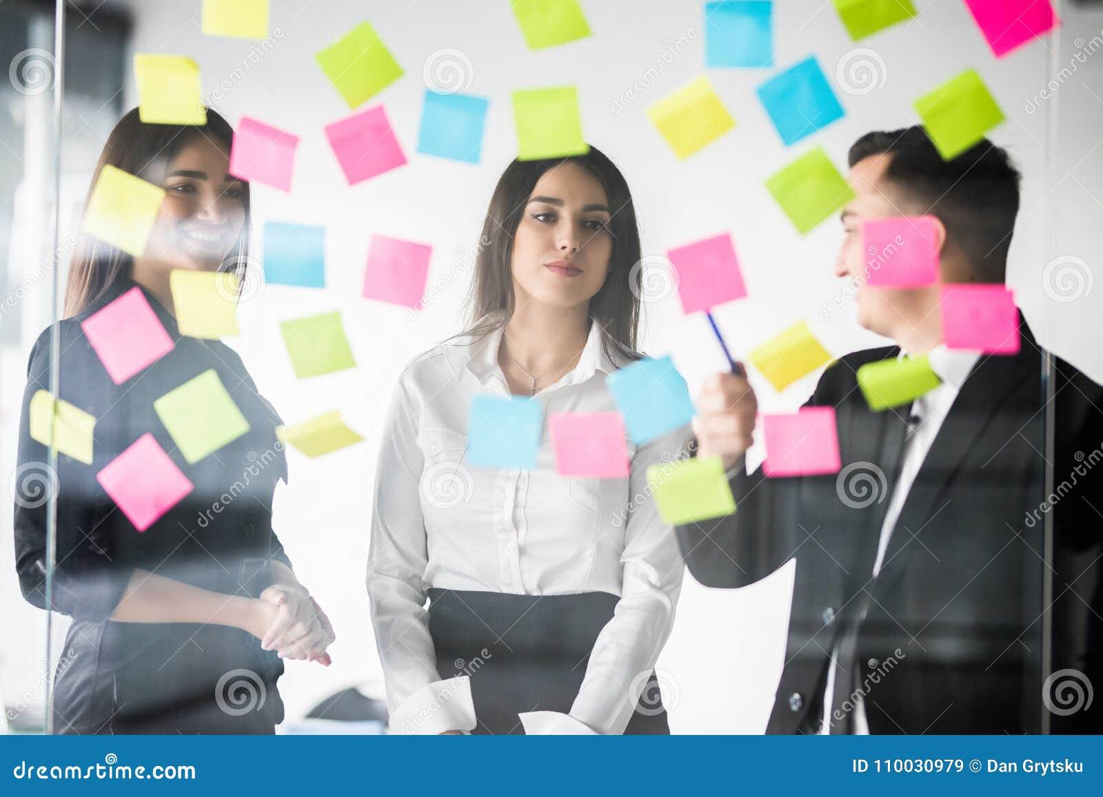 De mooie bedrijfsmensen gebruiken stickers en teller, bespreken ideeën en glimlachen tijdens de conferentie in bureau Het werk va