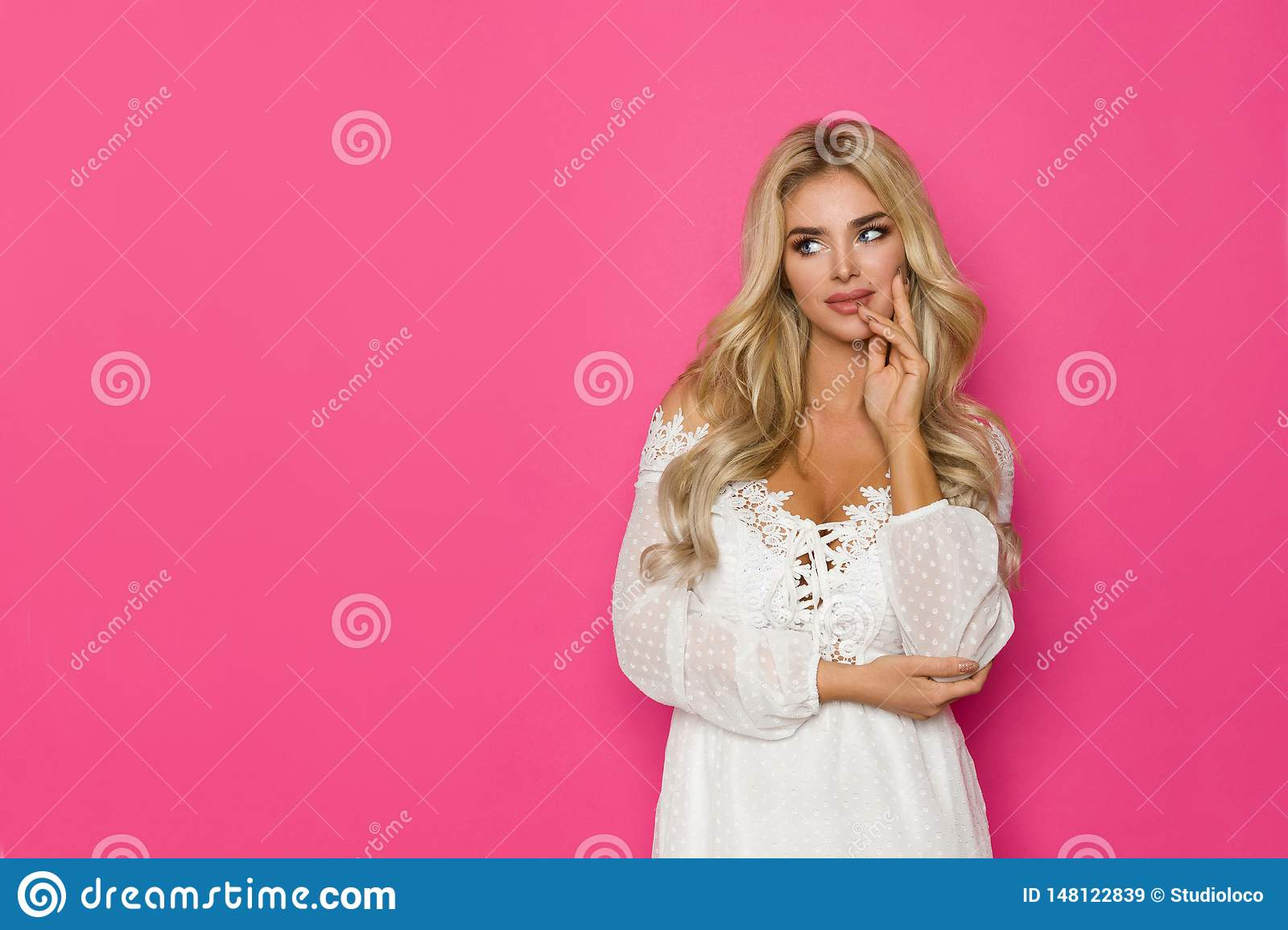 De mooie Blonde Vrouw in Witte Kleding is Holdingshand op Chin And Looking Away