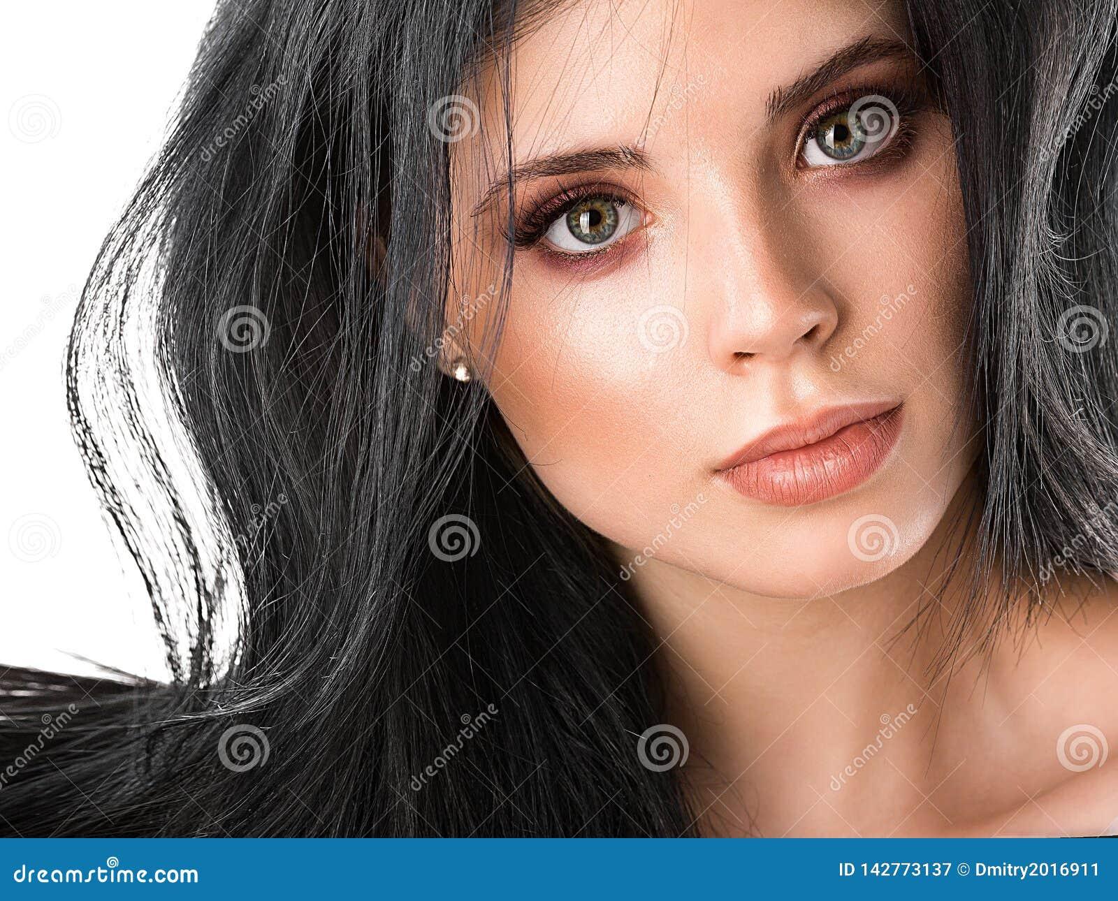 De mooie dichte omhooggaande studio van het donkerbruine vrouwengezicht op wit