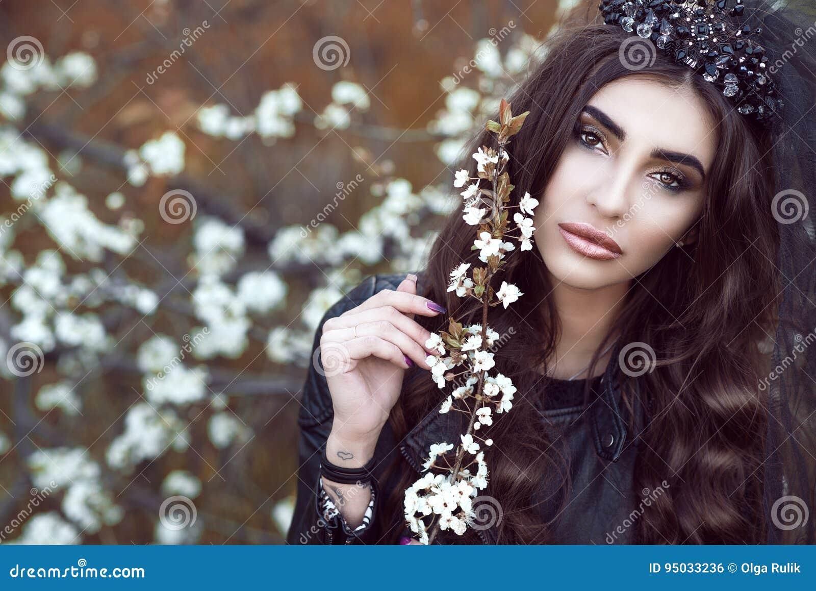 De mooie droevige donker-haired jonge vrouw met perfect maakt omhoog het dragen van zwarte juweelkroon met sluierholding tot bloe