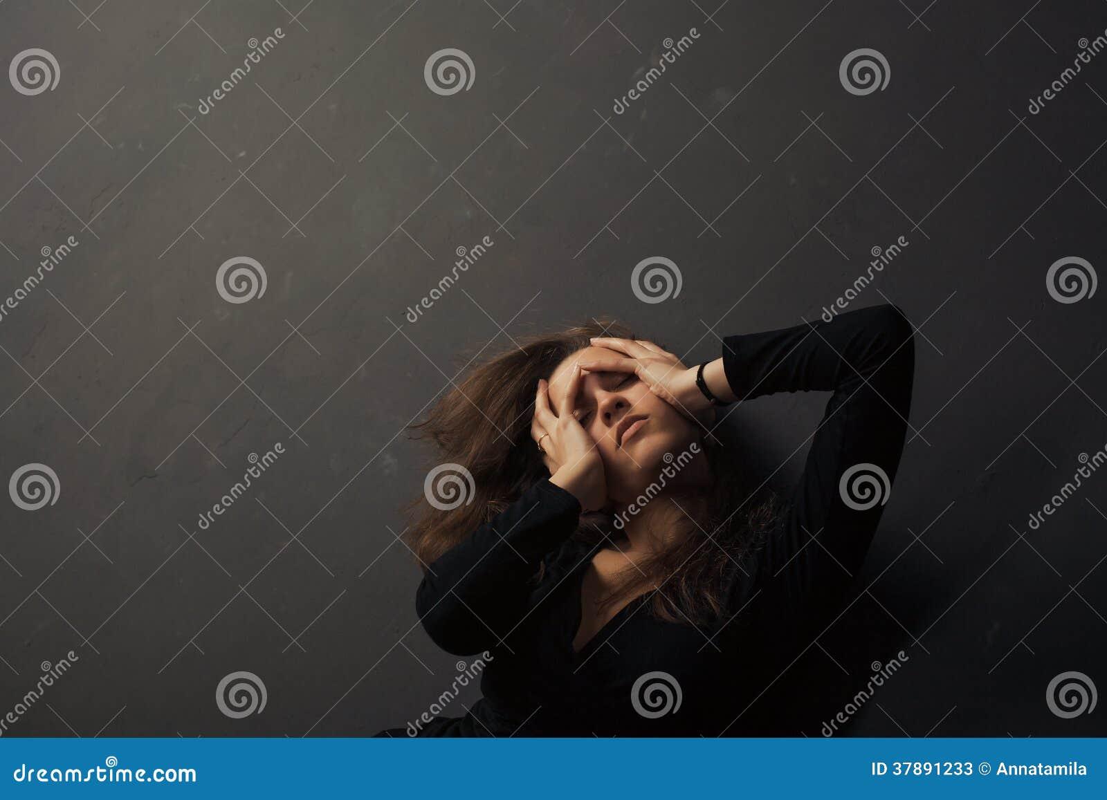 De mooie droevige jonge handen van de vrouwenholding op haar gezicht op een donkere achtergrond