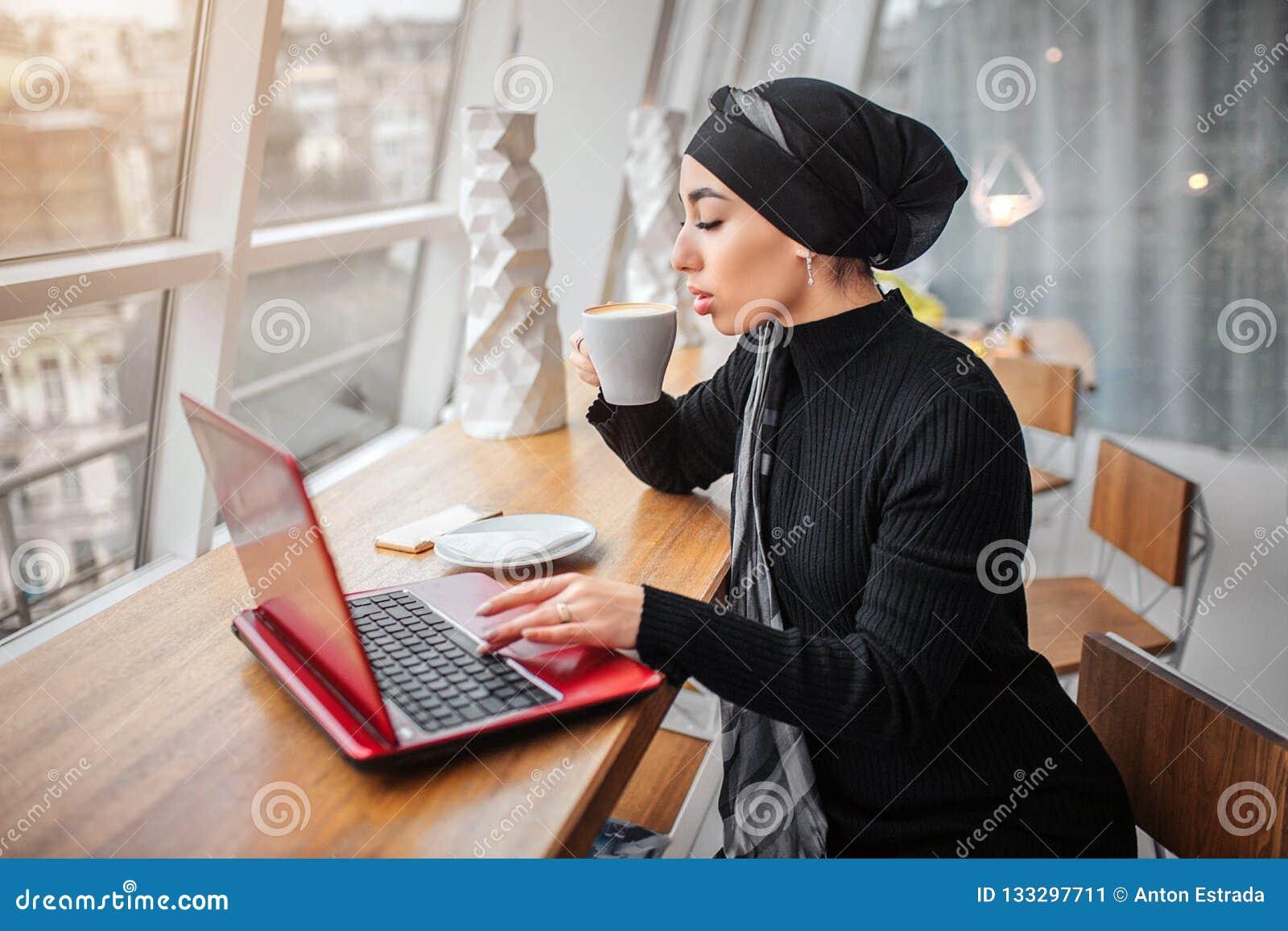 De mooie en goed-geklede jonge Arabische vrouw drinkt koffie en werkt aan laptop Zij zit binnen bij lijst Het is zonnig