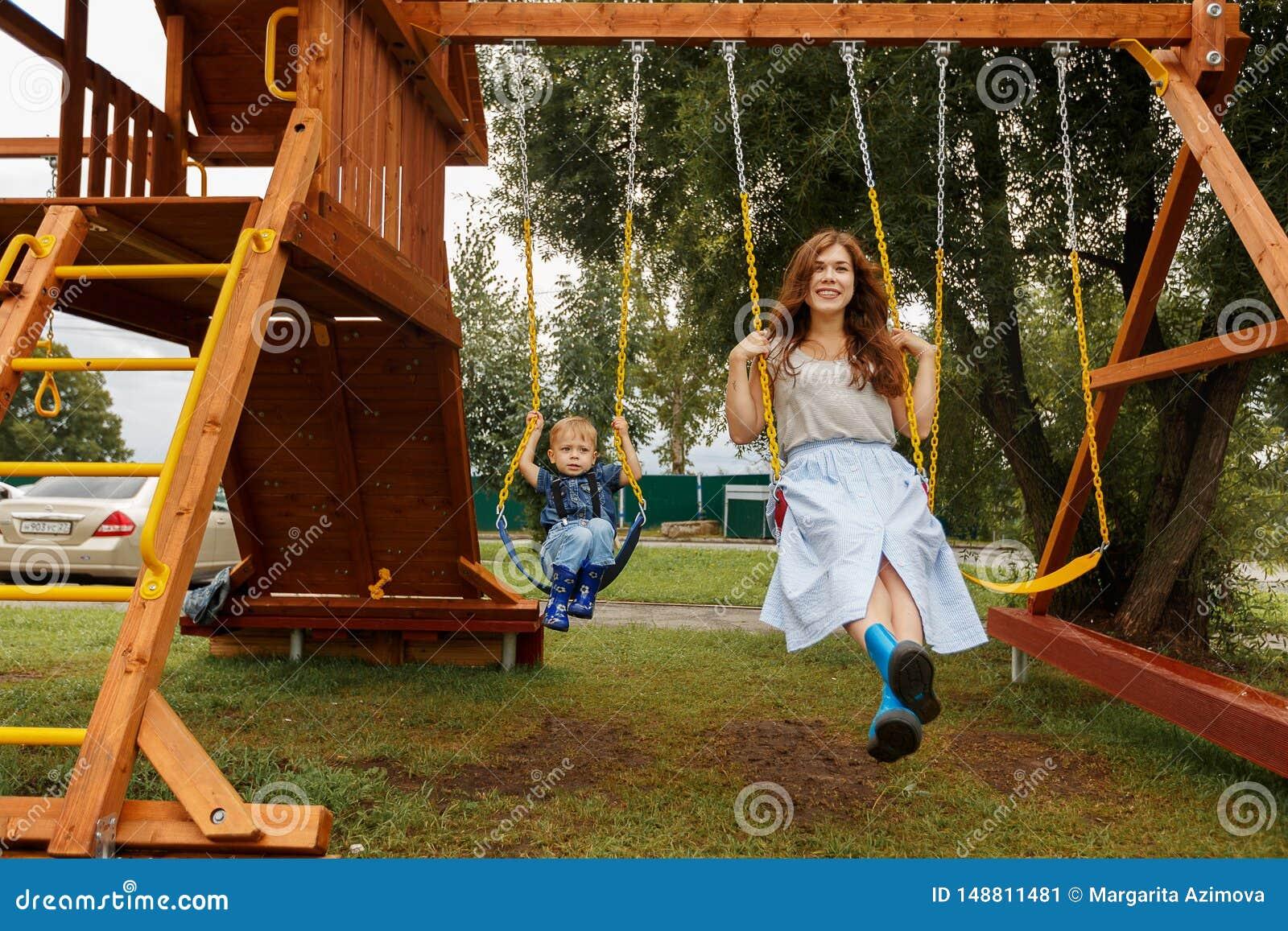 De mooie familie heeft buiten pret Ouders met kinderen die op een schommeling berijden Het mamma speelt met haar weinig zoon op e