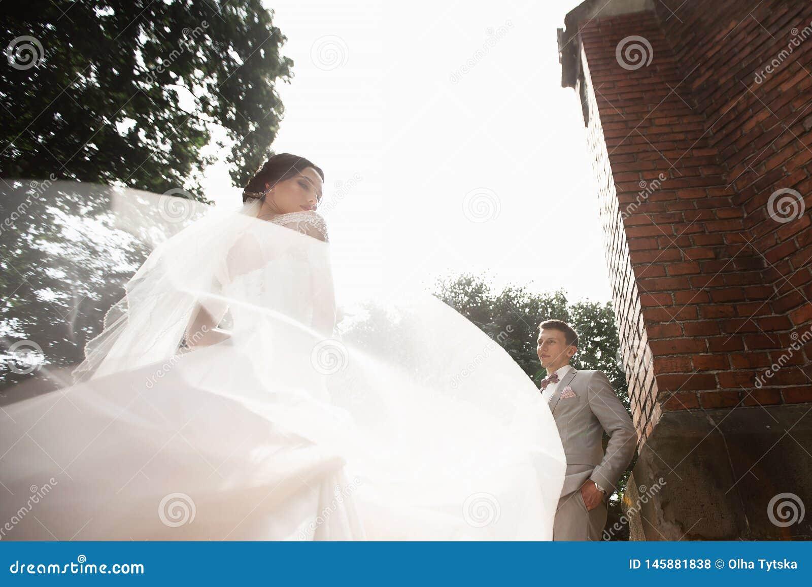 De mooie gang van het jonggehuwdepaar dichtbij oude christelijke kerk