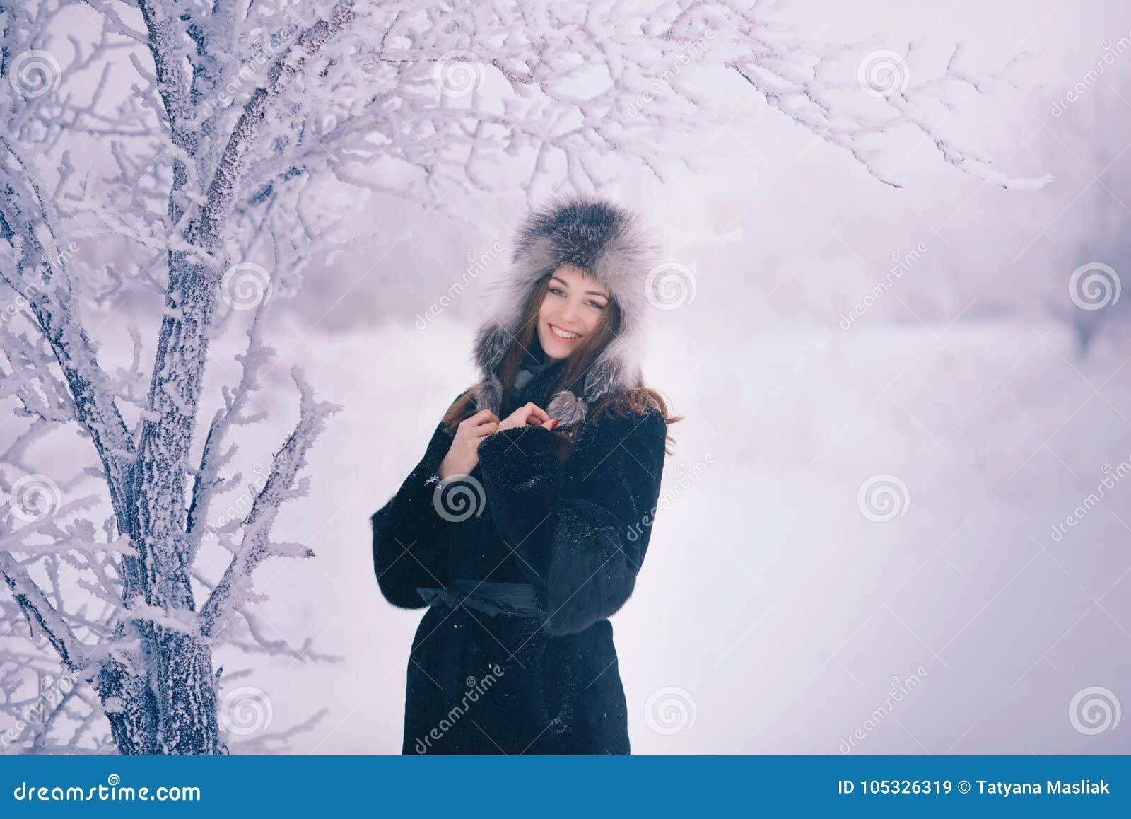 De mooie gelukkige lachende jonge vrouw die de handschoenen dragen die van de de winterhoed met sneeuw worden behandeld schilfert