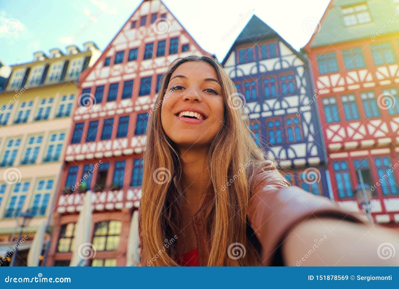 De mooie glimlachende vrouw neemt zelfportret in Romerberg-vierkant in Frankfurt, Duitsland